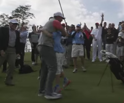 Tiger Woods hugs Taylor Crozier following his hole-in-one at the Woods-designed Bluejack National course (Photo: YouTube)