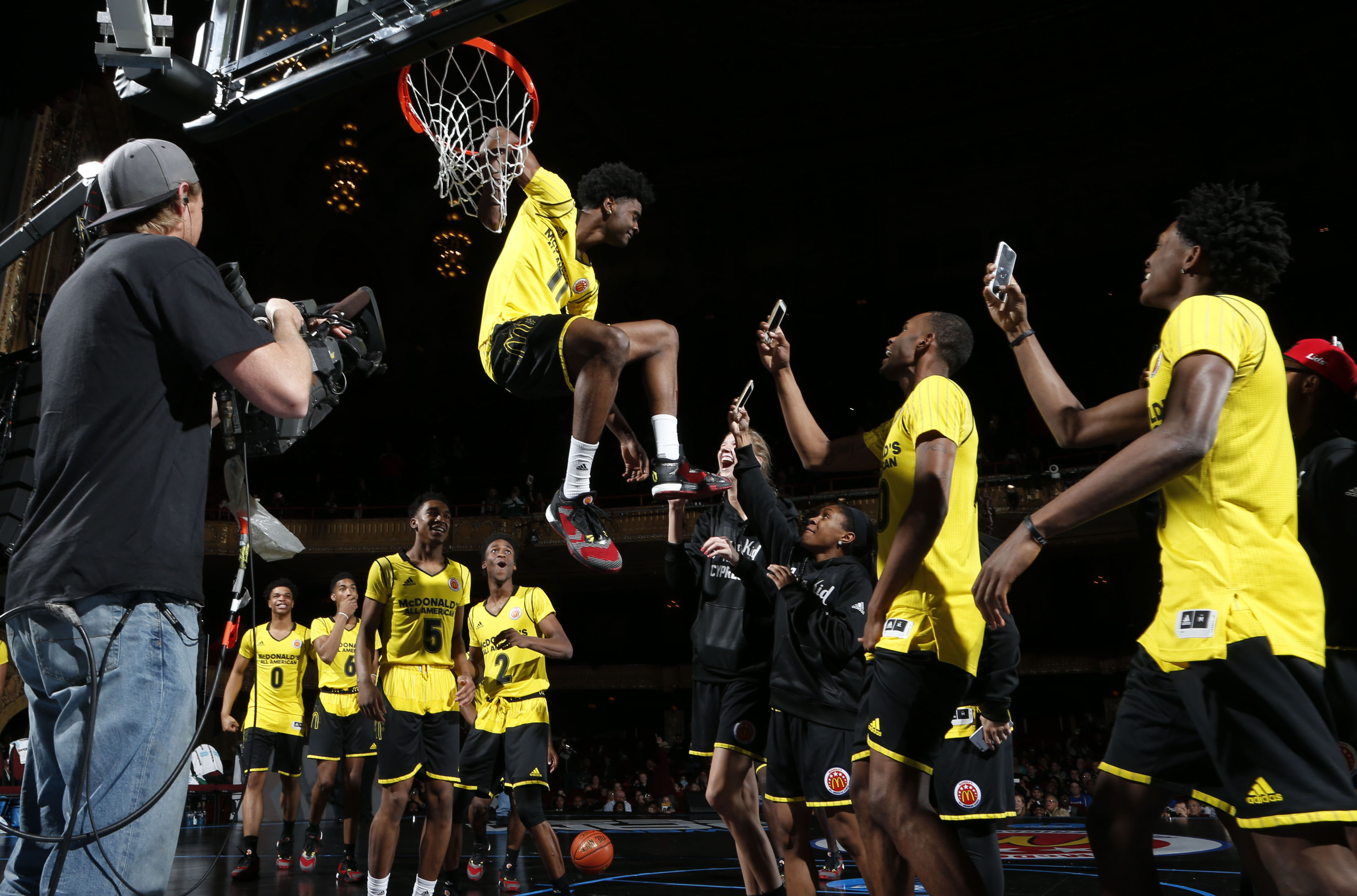 Josh Johnson hangs on the rim after dunking over Nancy Mulkey (Photo: Brian Spurlock, USA TODAY Sports)