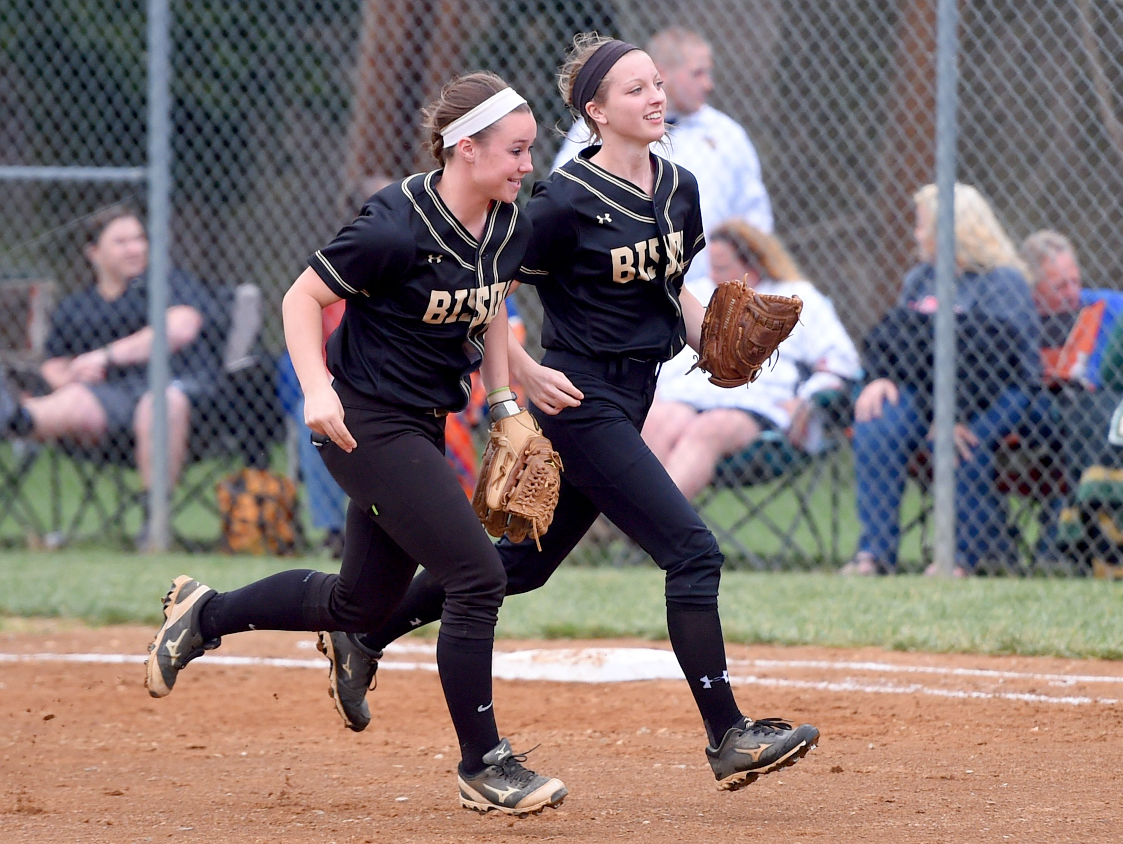 Buffalo Gap's Kieland Chandler (right) smiles as she heads to the dugout alongside teammate Amber Stokes after hustling to catch a pop-fly for the final out in the first inning during a softball game played in Fishersville on Friday, April 1, 2016.