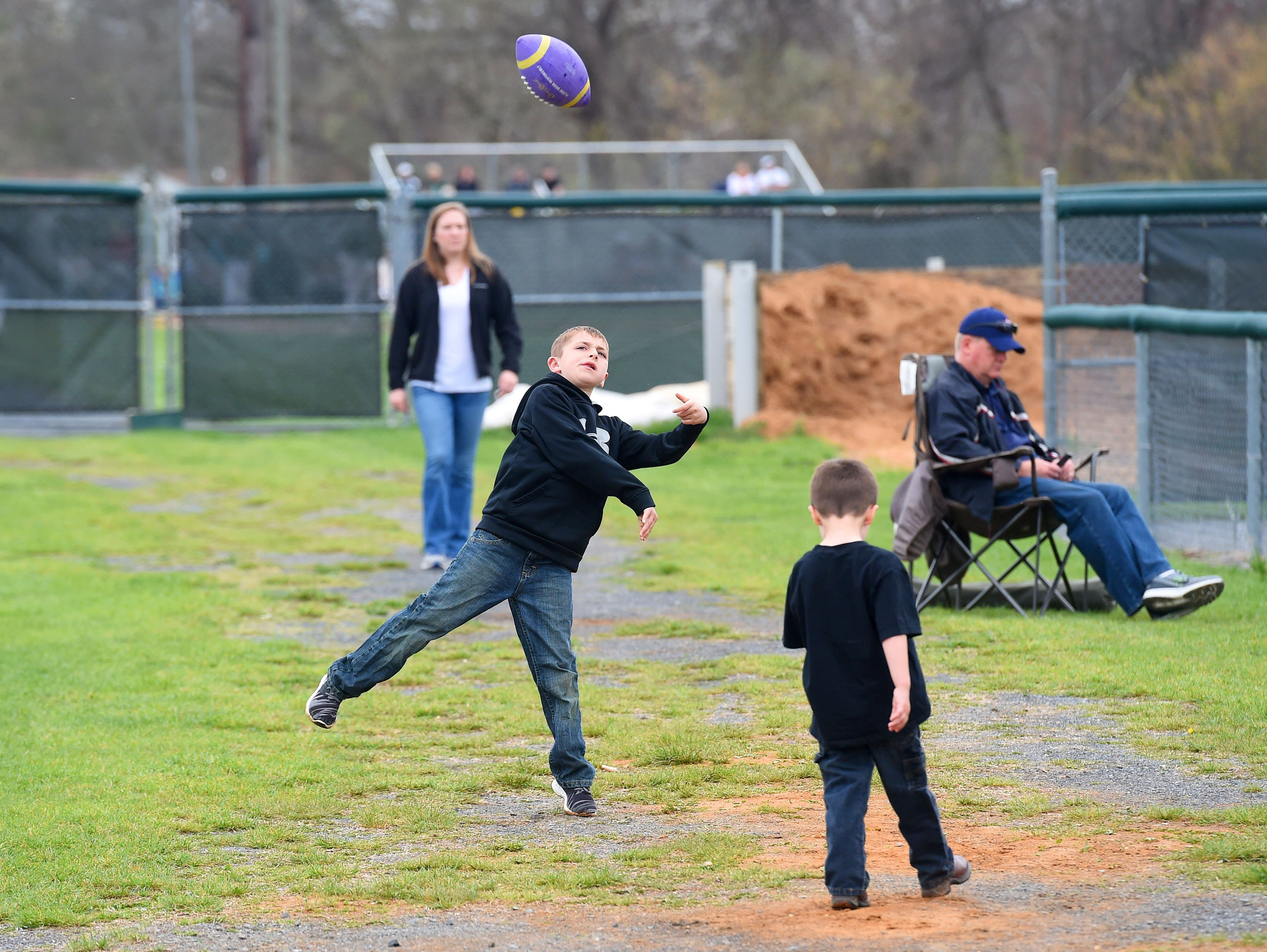 Tristan Clark, 9, of Churchville tosses the football with friends alongside the softball field before the start of a game between Buffalo Gap and Wilson Memorial high schools, played in Fishersville on Friday, April 1, 2016.