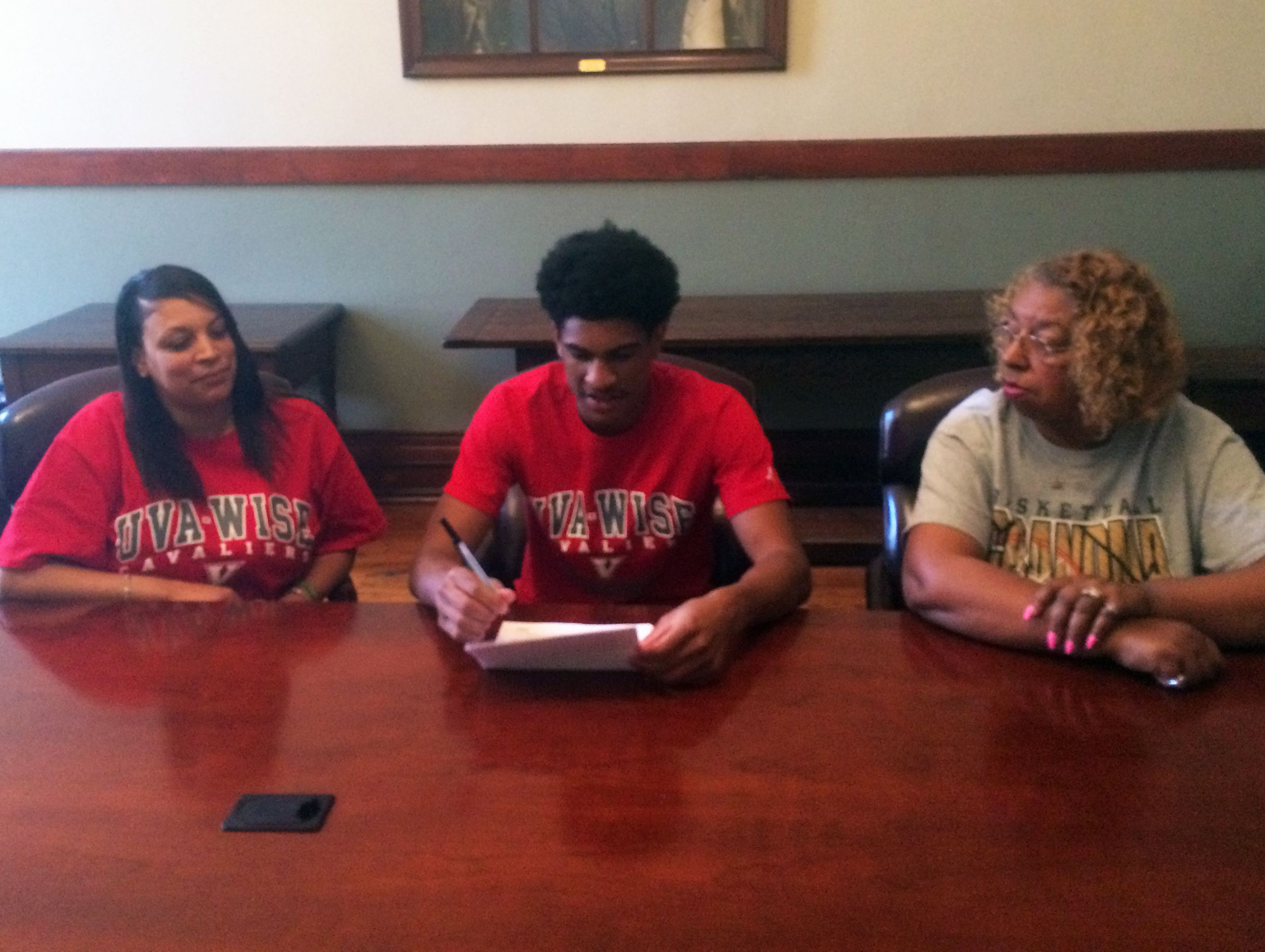 The Miller School's Chance Sheffey, middle, signs his scholarship offer to U.Va.-Wise on Friday. His mom, Trina Sheffey, left, and grandmother Rebecca Johnson joined him at the signing.