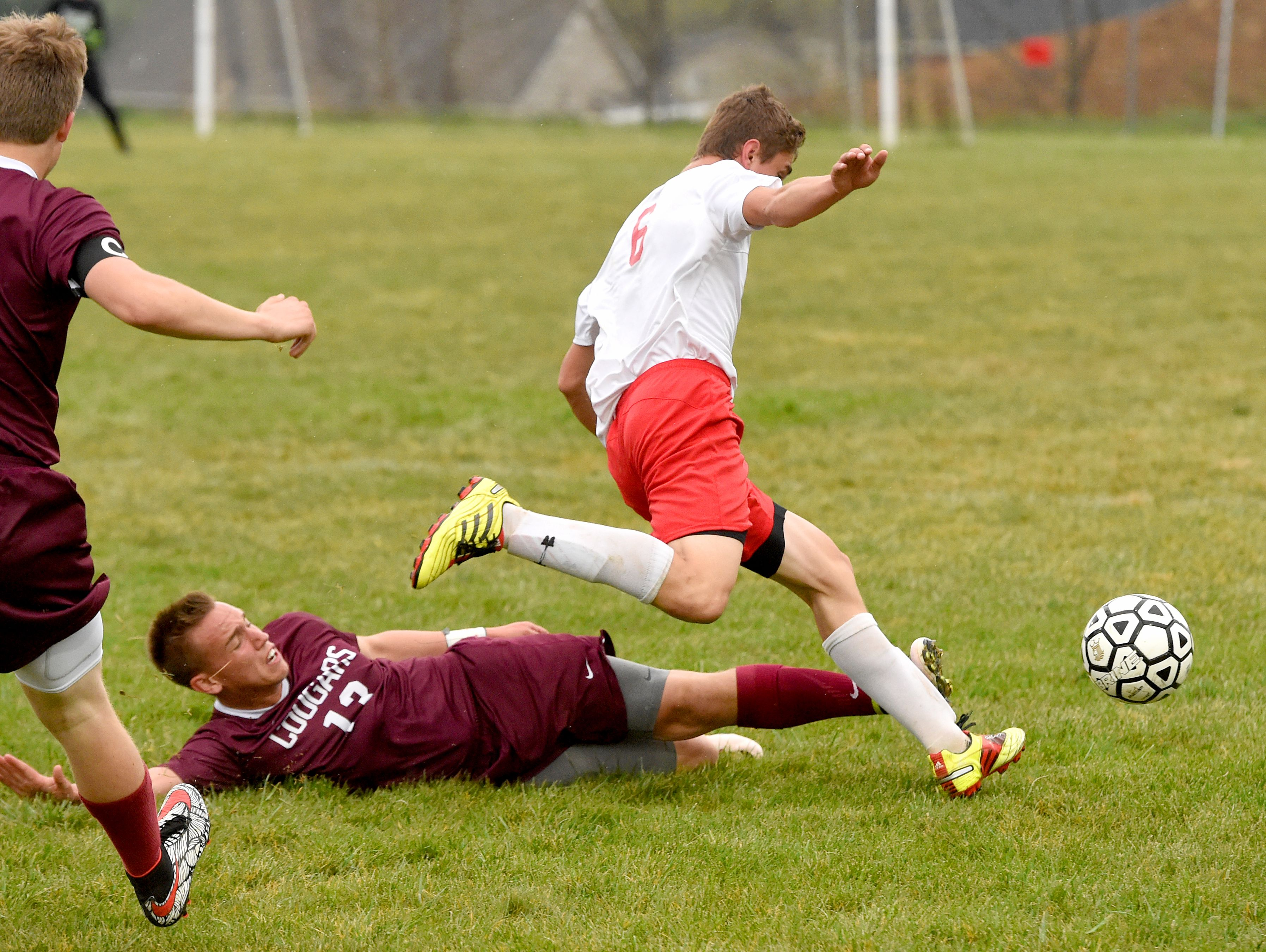 Riverheads' Jason Burch moves to kick the ball as he slips past Stuarts Draft's Joshua Huff who has gone down during a soccer game played in Greenville on Friday, April 22, 2016.