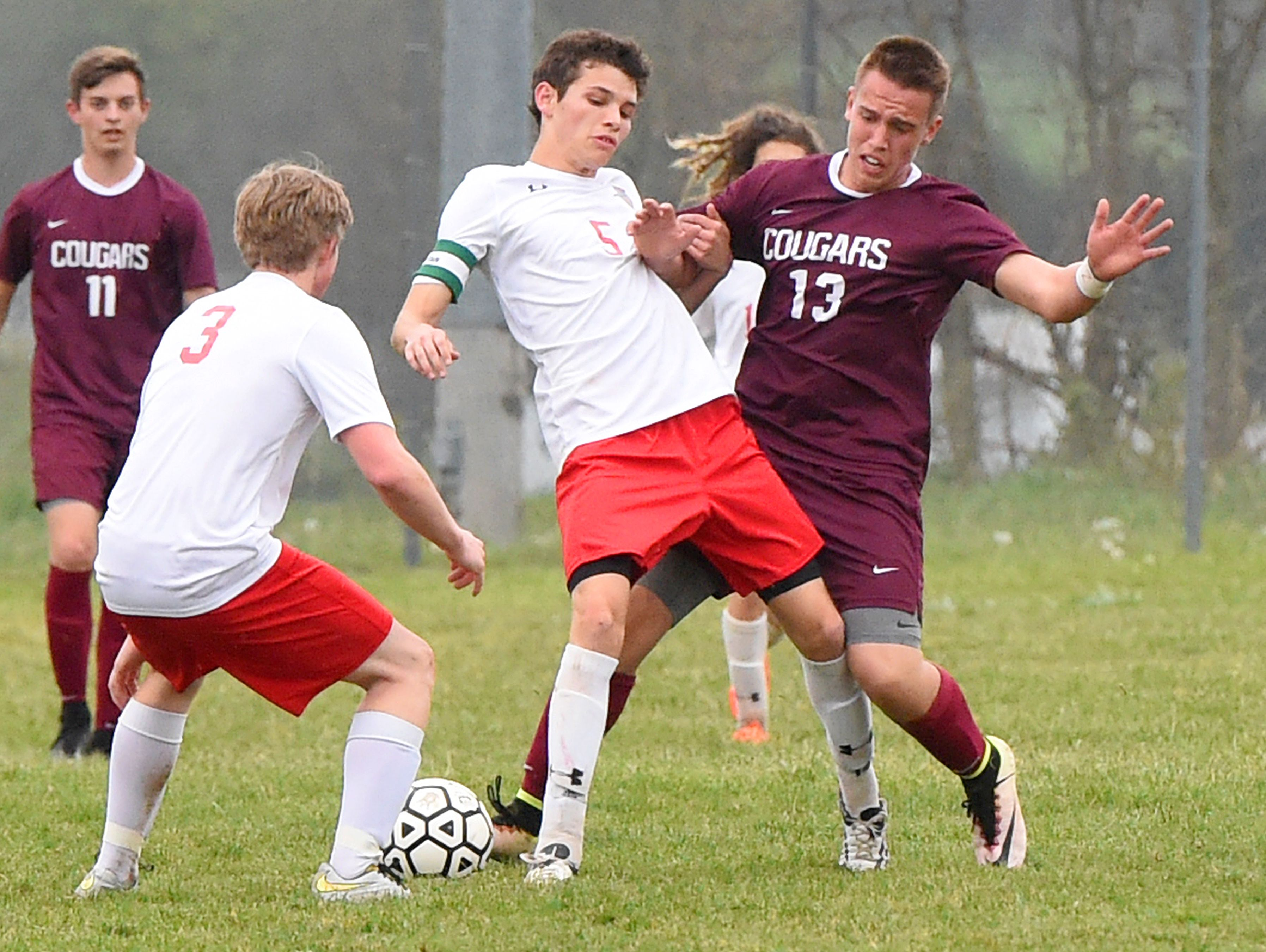 Riverheads' Elijah Knopp (center) tries to keep Stuarts Draft's Joshua Huff away from the ball as they battle for control of it during a soccer game played in Greenville on Friday, April 22, 2016.