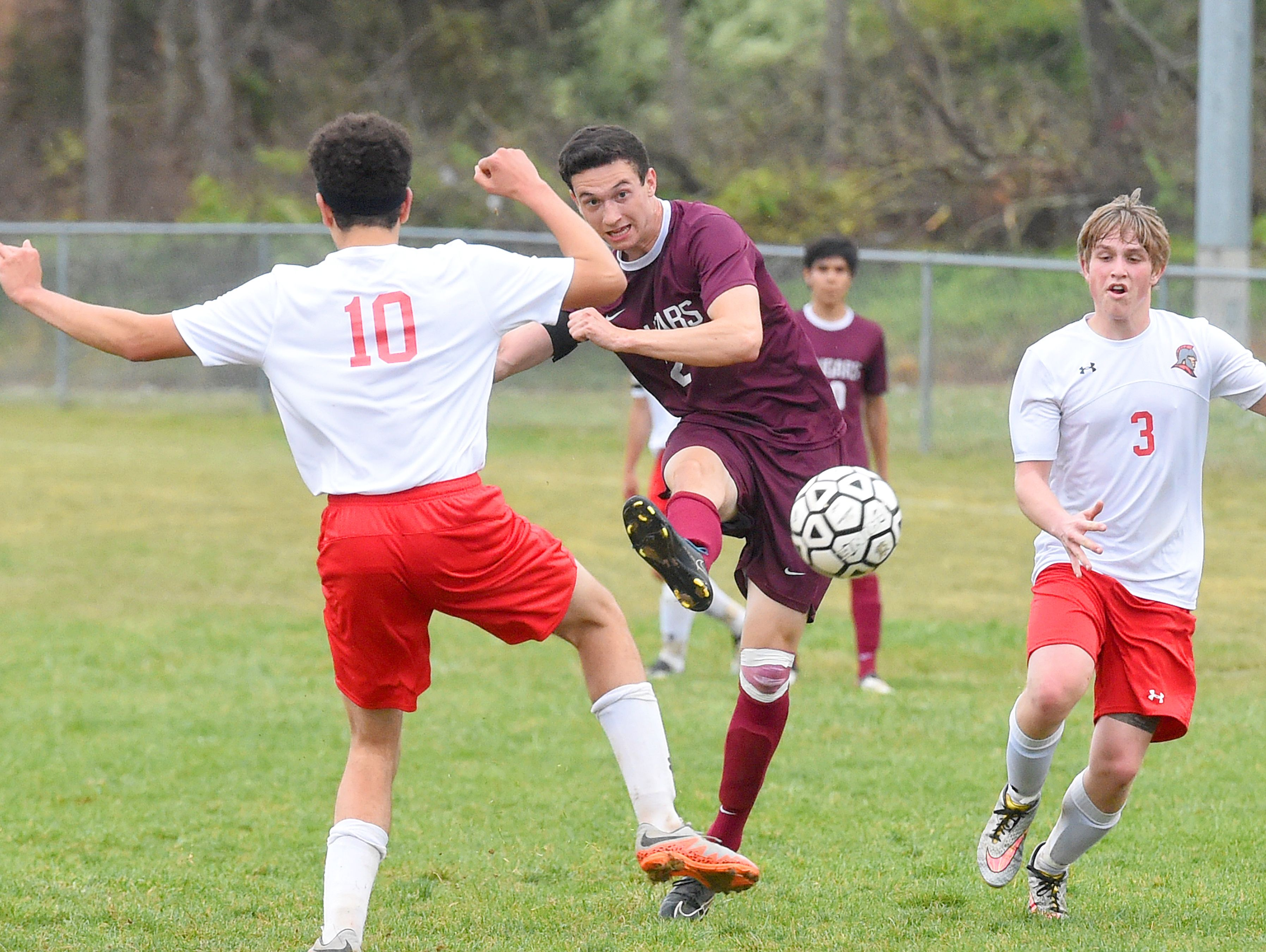 Stuarts Draft's Caleb Oakes kicks the ball as he faces off against Riverheads' DeyShon Hartley in front of him and William Elkins beside him during a soccer game played in Greenville on Friday, April 22, 2016.