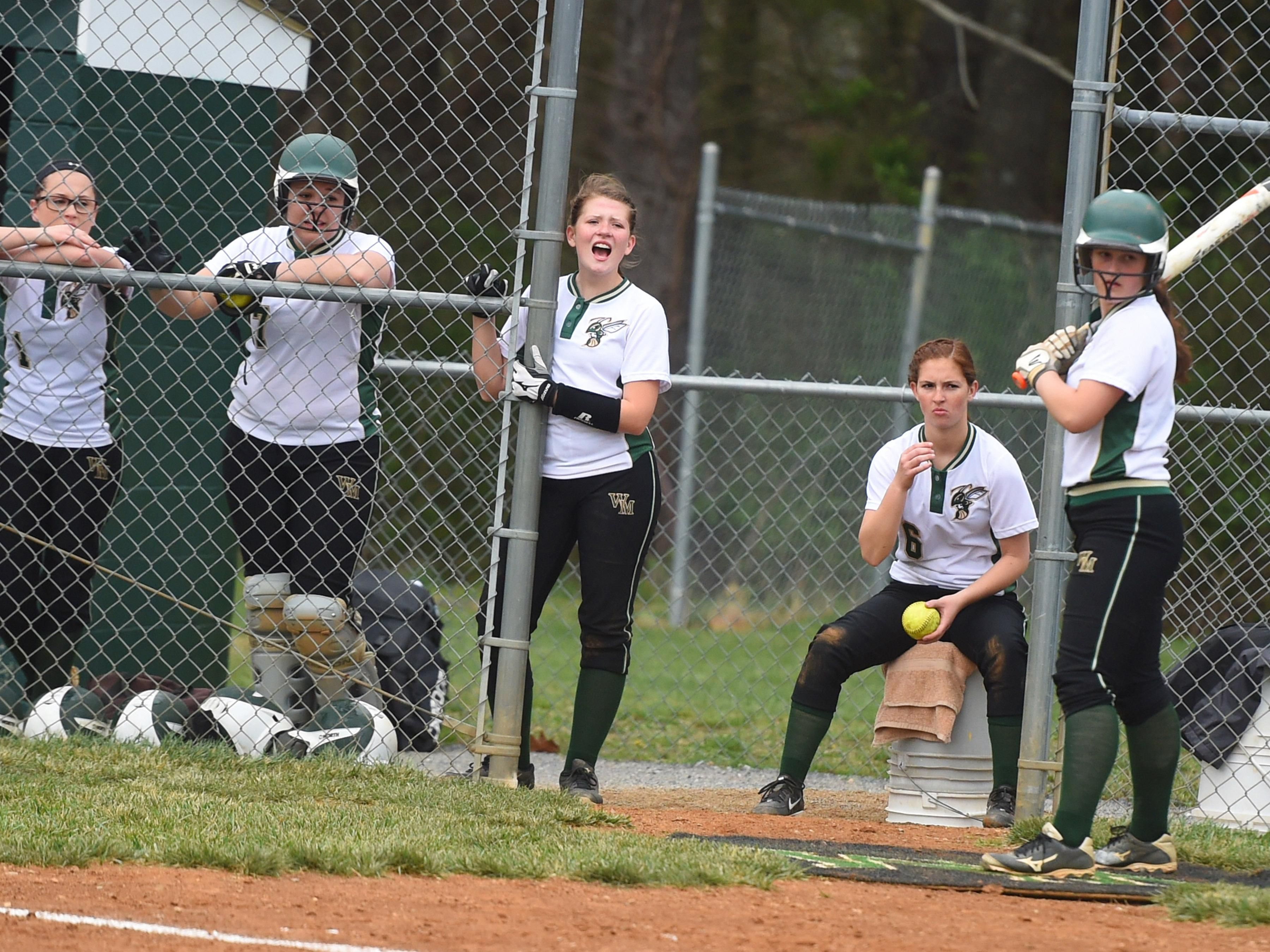 Wilson Memorial's Emma Peery (center) joins teammates in cheering on their batter in the first inning during a softball game played in Fishersville on Friday, April 1, 2016.