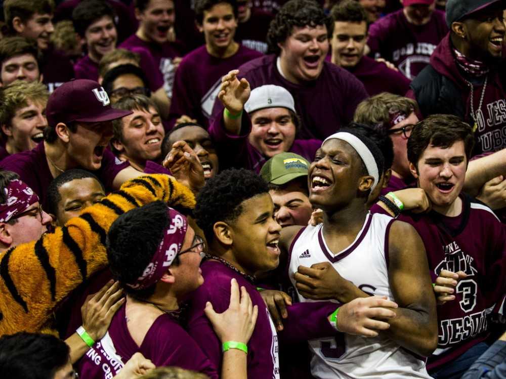 Detroit U-D Jesuit's Cassius Winston dives into the student section as they celebrate defeating North Farmington f the Class A boys high school basketball state championship game. (Photo: Associated Press).