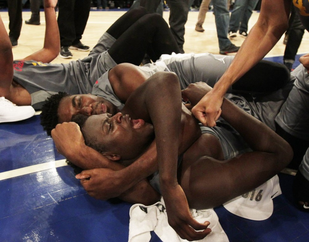 Oak Hill (Mouth of Wilson, Va.) players surround Khadim Sy (on ground) after his tip-in gave the Warriors a 62-60 overtime defeat of La Lumiere (La Porte, Ind.) in the championship of the DICK'S Sporting Goods High School Nationals. (Photo: Andy Marlin, USA Today Sports Images).