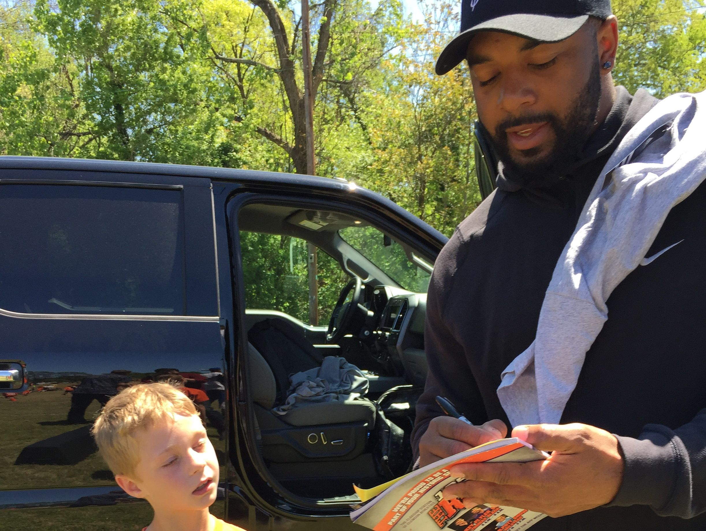 Former Clemson quarterback Tajh Boyd signs an autograph for a young man during his recent football camp in Greenville.