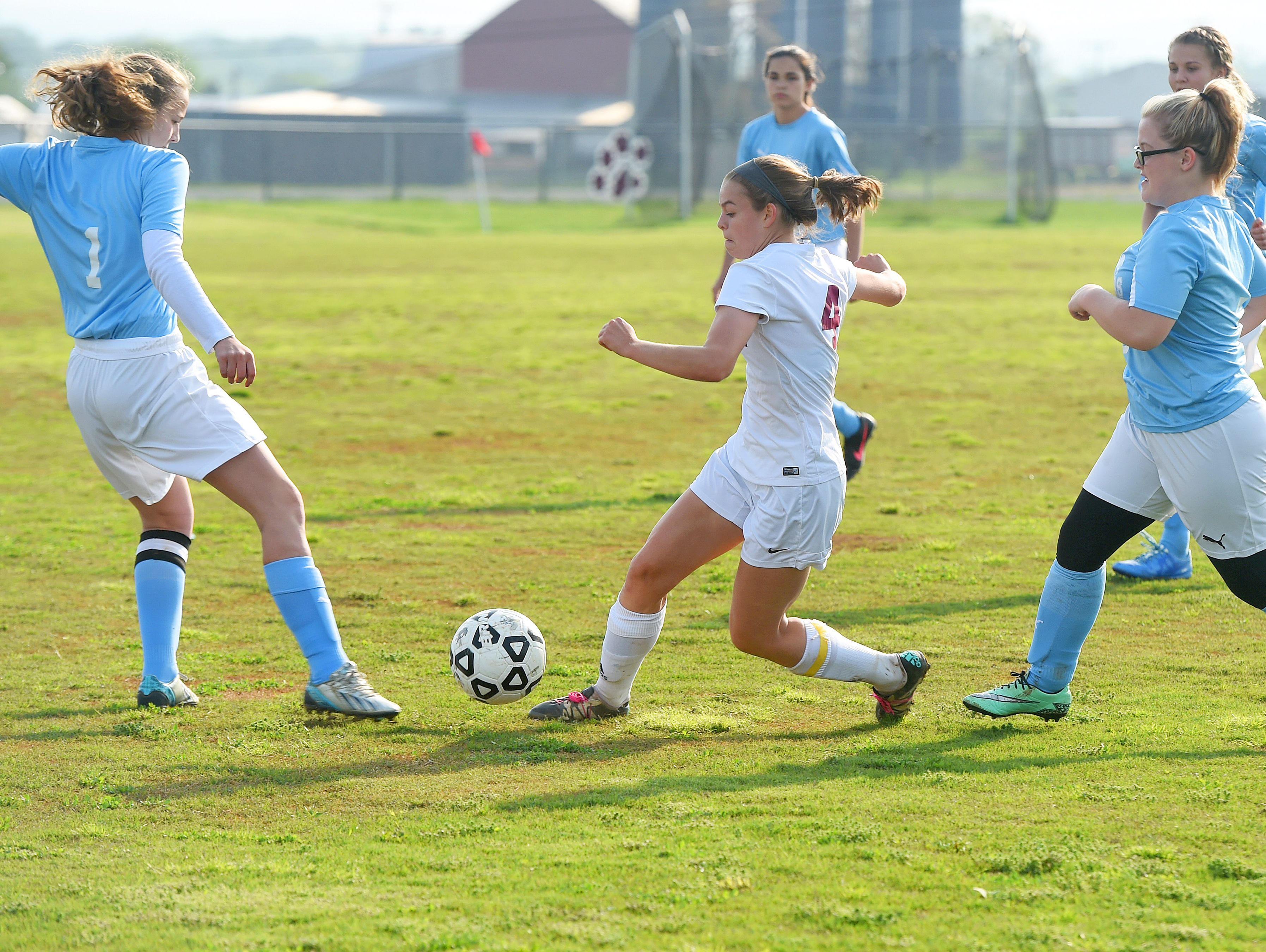 Stuarts Draft's Rachel Sauder (center) battles Page County's Brianna Good for control of the ball and will kick it for a goal during a soccer match played jn Stuarts Draft onTuesday, May 10, 2016.