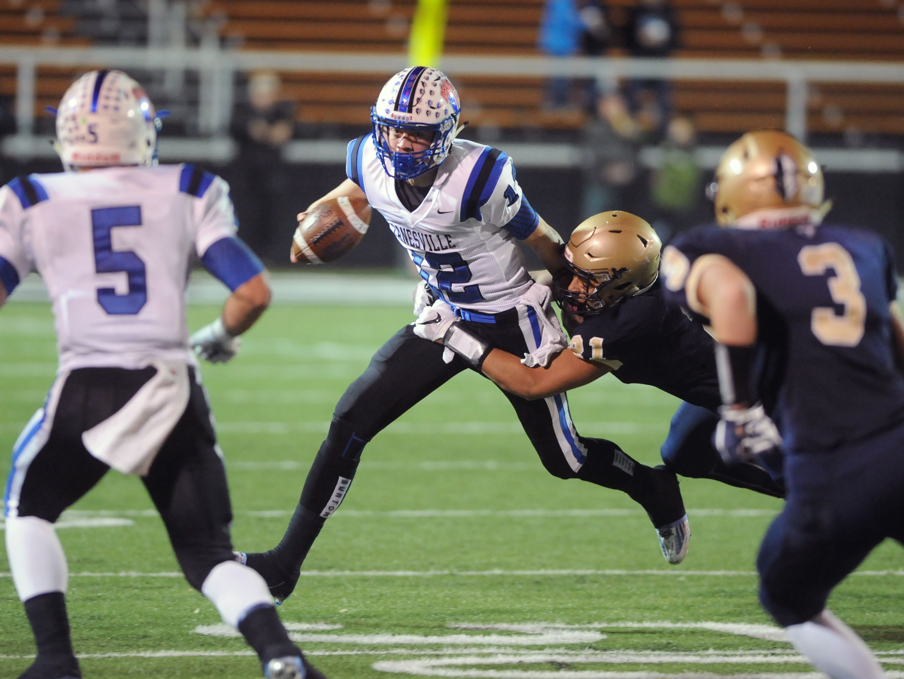 Akron Hoban's Tyler Gilchrist pulls down Zanesville's Derek Grandstaff on Friday night during the Division III state semifinals in Massillon. The Blue Devils' fell to the Knights, 33-21.