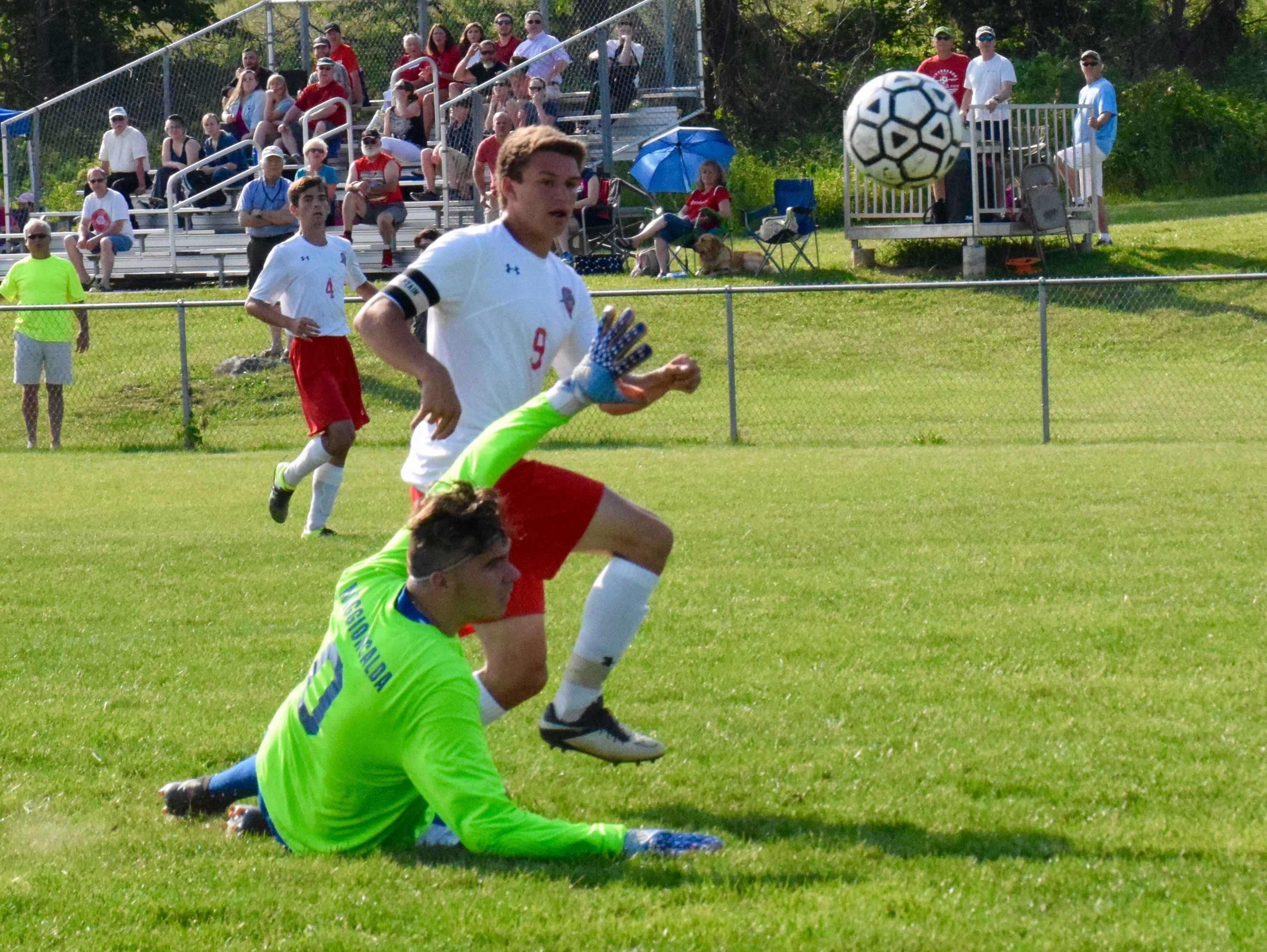 Riverheads' James Kasak nudges the ball past Mathews keeper Joseph Maggioncalda for a goal during the first half of the Gladiators' Region 1A East semifinal on Wednesday, June 1, 2016, at Riverheads High School in Greenville.