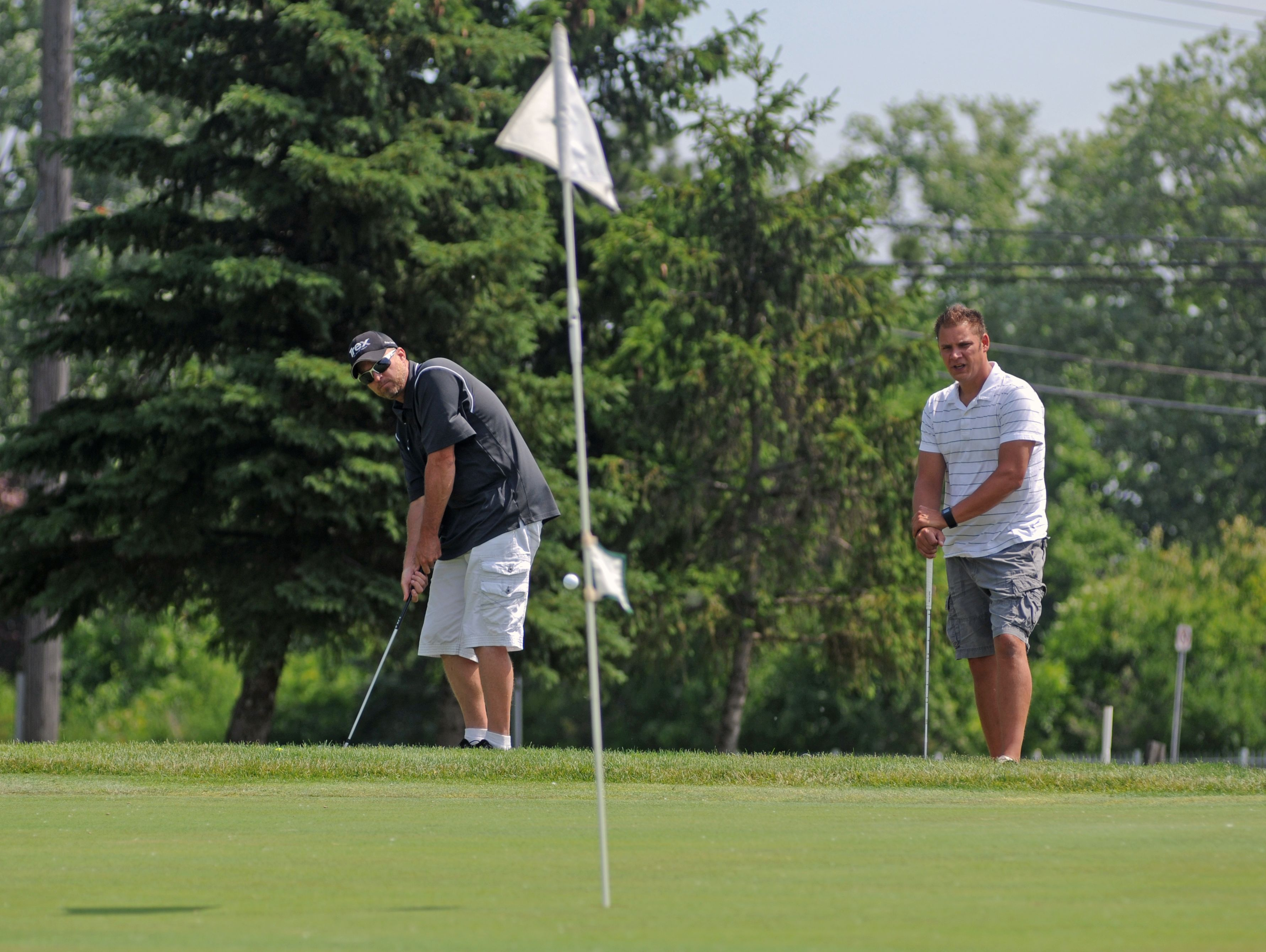 Scott Schoof, of Richmond, chips on as Matt Puwal, of Columbus Township watches Monday, June 20, during the Lelito Legacy Golf Outing at St. Clair Golf Cub.