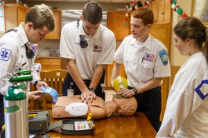 Dec 20, 2014; Darien, CT, USA; EMS Post 53 vice pres of EMS Training and Darien High School swimmer Nicolai Ostberg (left), twin brother post 53 Cruise Officer & Darien High School cross country runner Alex Ostberg (2nd right), EMS student president & Darien High School track & field runner Arthur Cassidy (2nd left) and EMS Rider, high school student Emily Gianunzio (right) practice their CPR skills at Post 53 in Darien, CT Saturday morning during their on-call shift. Mandatory Credit: David Butler II-USA TODAY Sports ORG XMIT: US 132289 Alex Ostberg 12/20/2014 [Via MerlinFTP Drop]