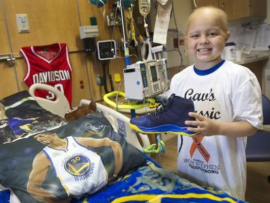 Brody Stephens, 7, poses by his Golden State-themed bed with new Steph Curry basketball shoes at Riley Hospital for Children, Wednesday, July 13, 2016. A friend from Brody's baseball league gave them to him as a gift, since he wouldn't be able to play this season. Stephen is battling leukemia for a second time. (Photo: Jenna Watson/IndyStar)