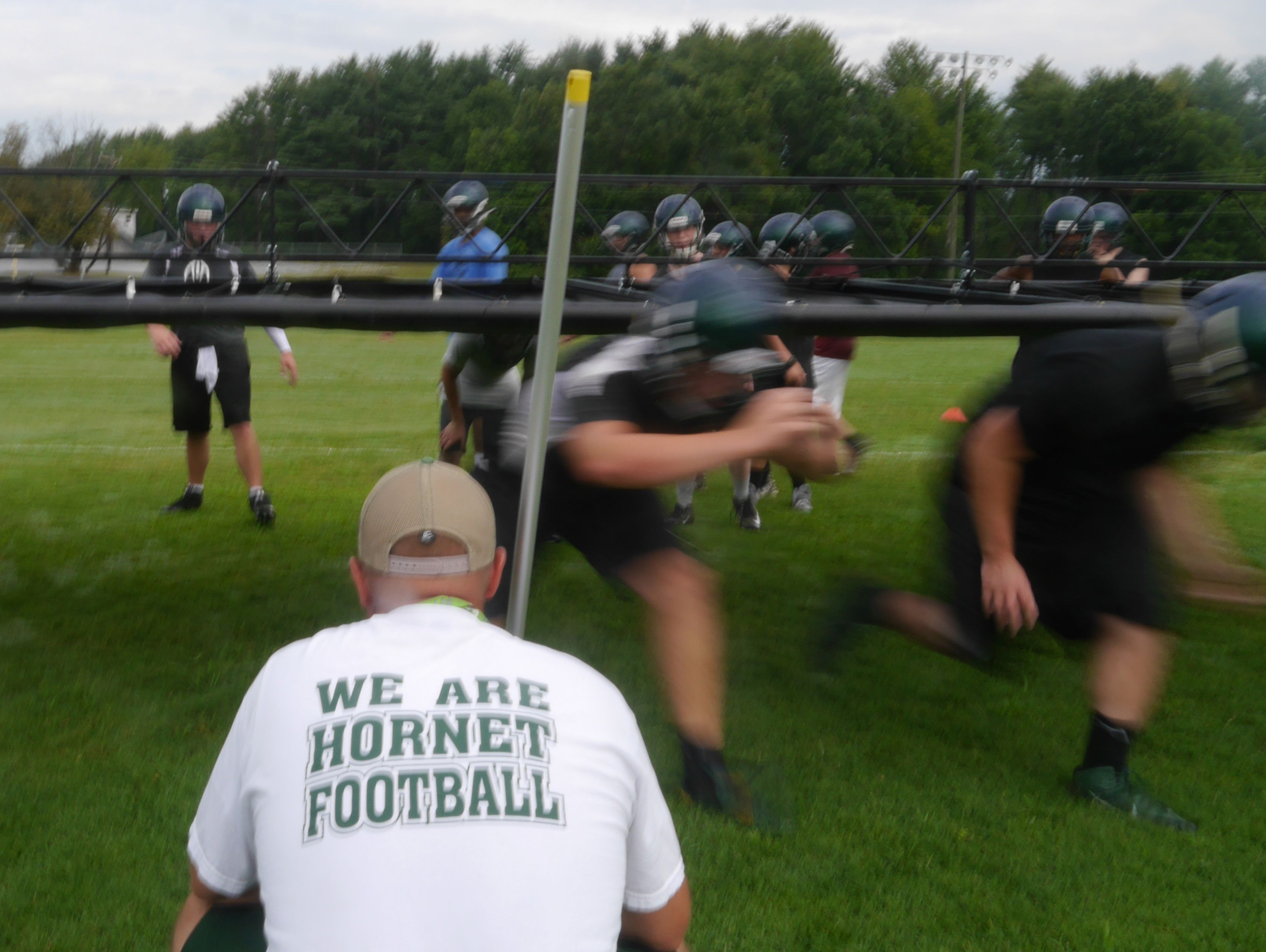 Wilson Memorial High School football coach Jeremiah Major runs lineman drills during the first day of practice on Thursday, July 28, 2016.