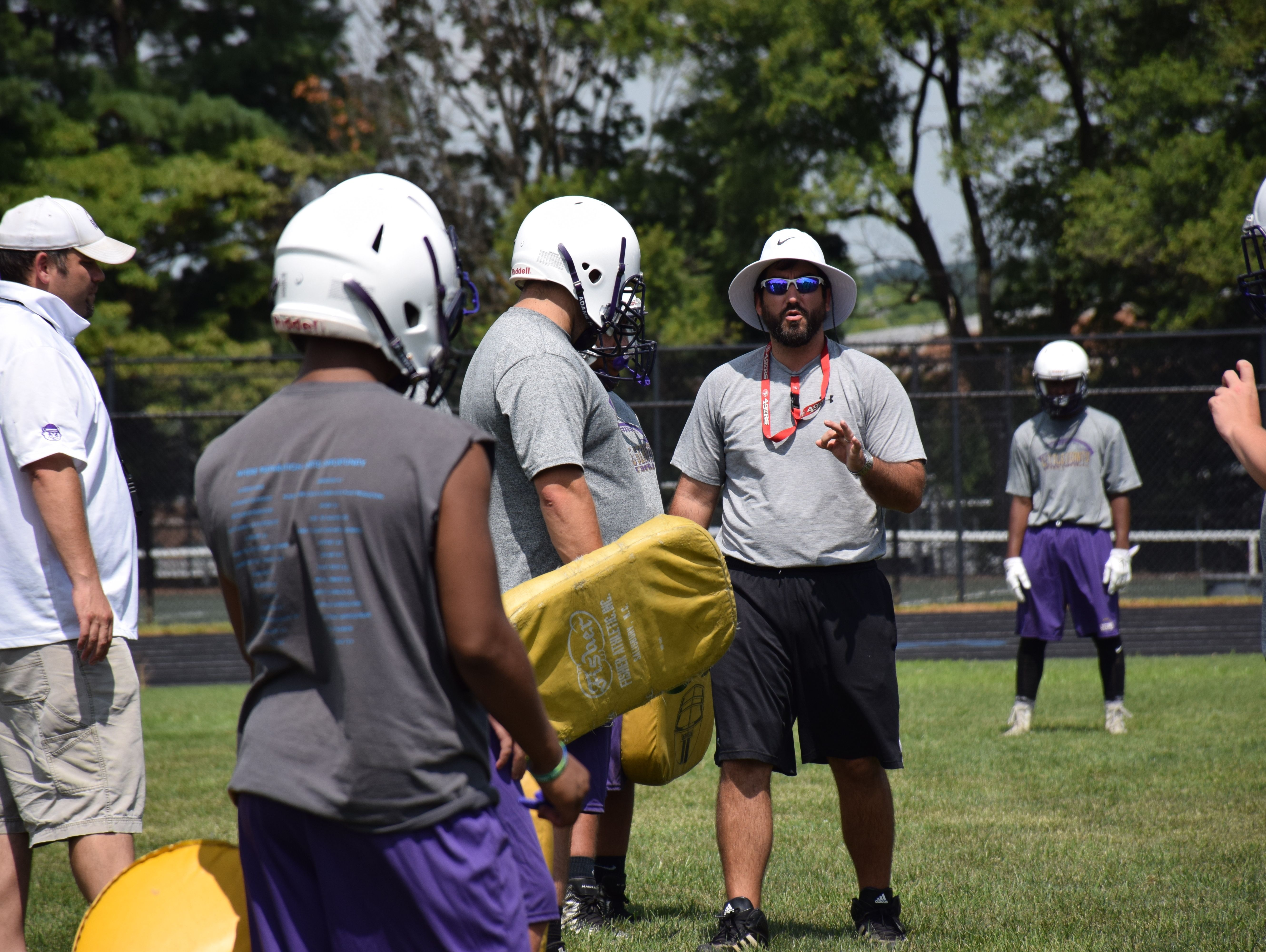 Waynesboro assistant coach Shawn Moran guides the Little Giants though an offensive drill during the first day of practice on Thursday, July 28, 2016, at Waynesboro High School