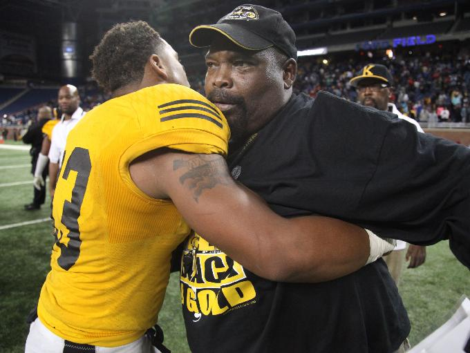 Detroit King coach Dale Harvel hugs players at Ford Field in Detroit on Oct. 23, 2015.