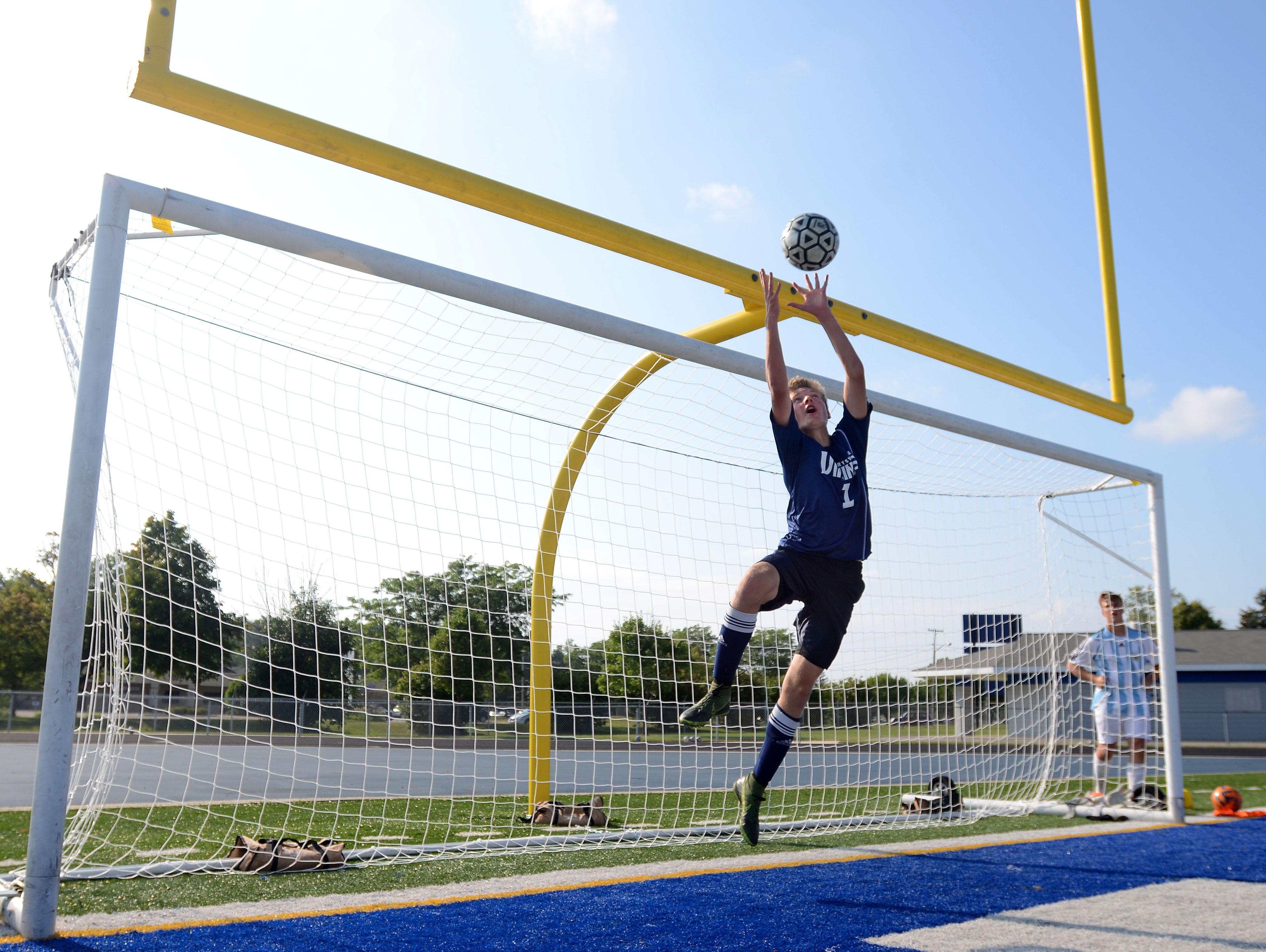 Goalkeeper Brett Robinson leaps to make the save Tuesday, Aug 18, during soccer practice at Walt Braun Stadium at Marysville High School.
