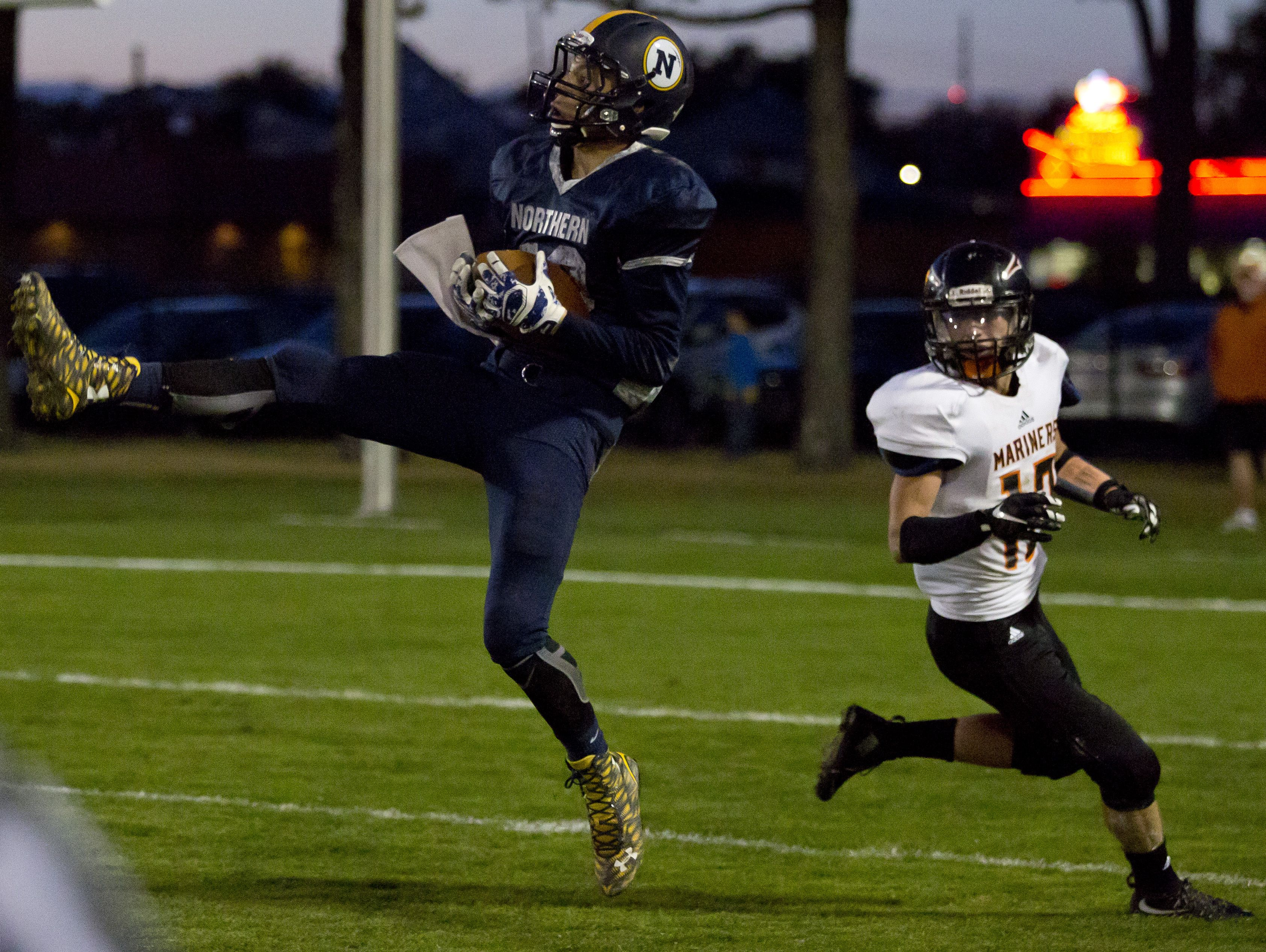 Port Huron Northern senior Geyrd Welsh catches a pass in front of Marine City junior Ryan Alexander during a football game Friday, October 9, 2015 at Memorial Stadium in Port Huron.