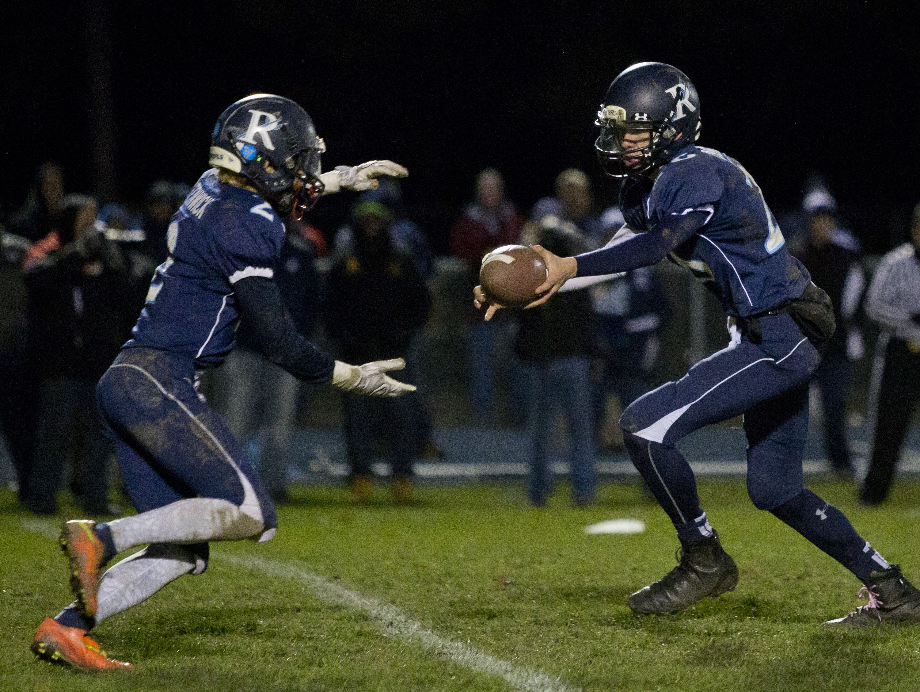 Richmond's Chase Churchill hands off the ball to Stefan Fenwick during a regional final football game Friday, November 13, 2015 at Richmond High School.