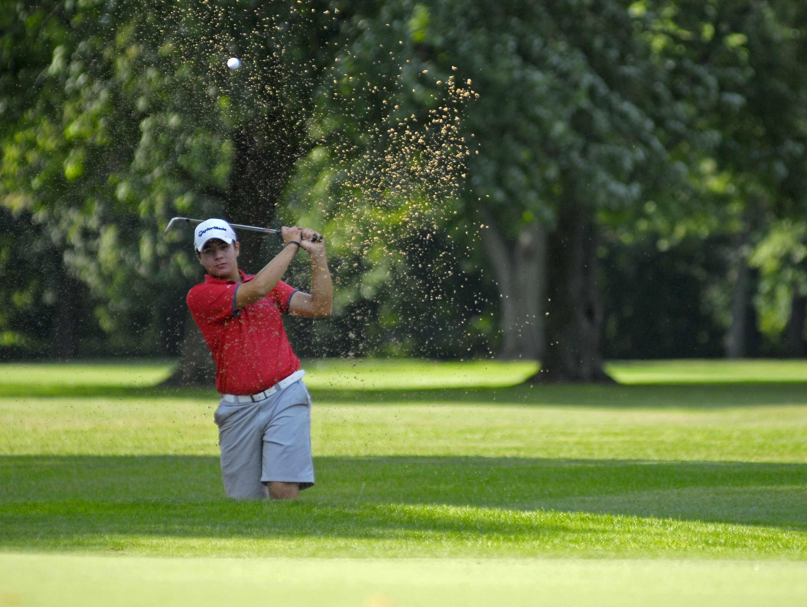 Matthew Bayer, of Macomb, hits out of the sand Monday, Aug 1, during the Tournament of Champions at the Port Huron Elks Golf Course.