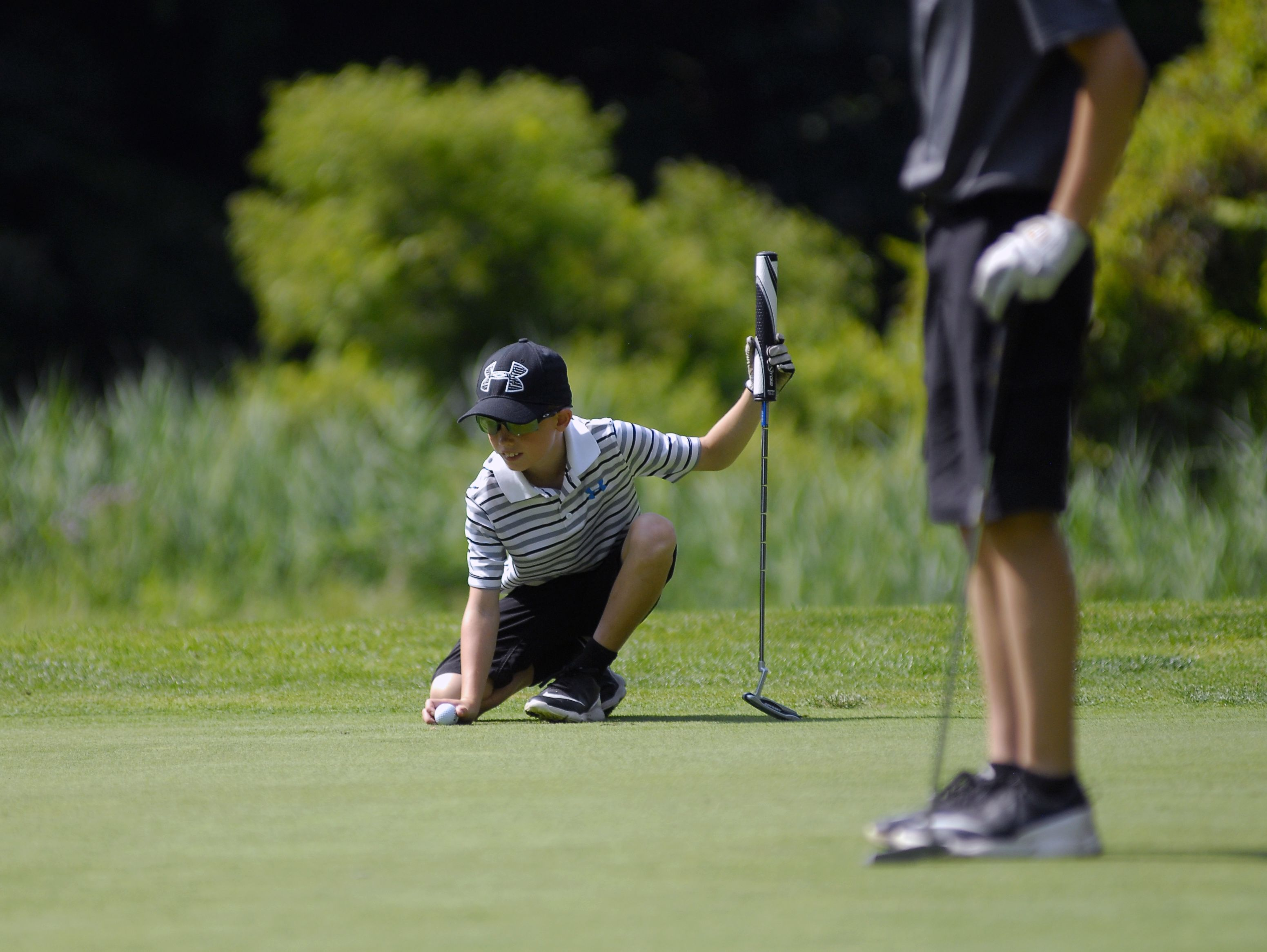 Kyren Bruno, 10, of Jeddo, lines up his putt Monday, Aug 1, during the Tournament of Champions at the Port Huron Elks Golf Course.