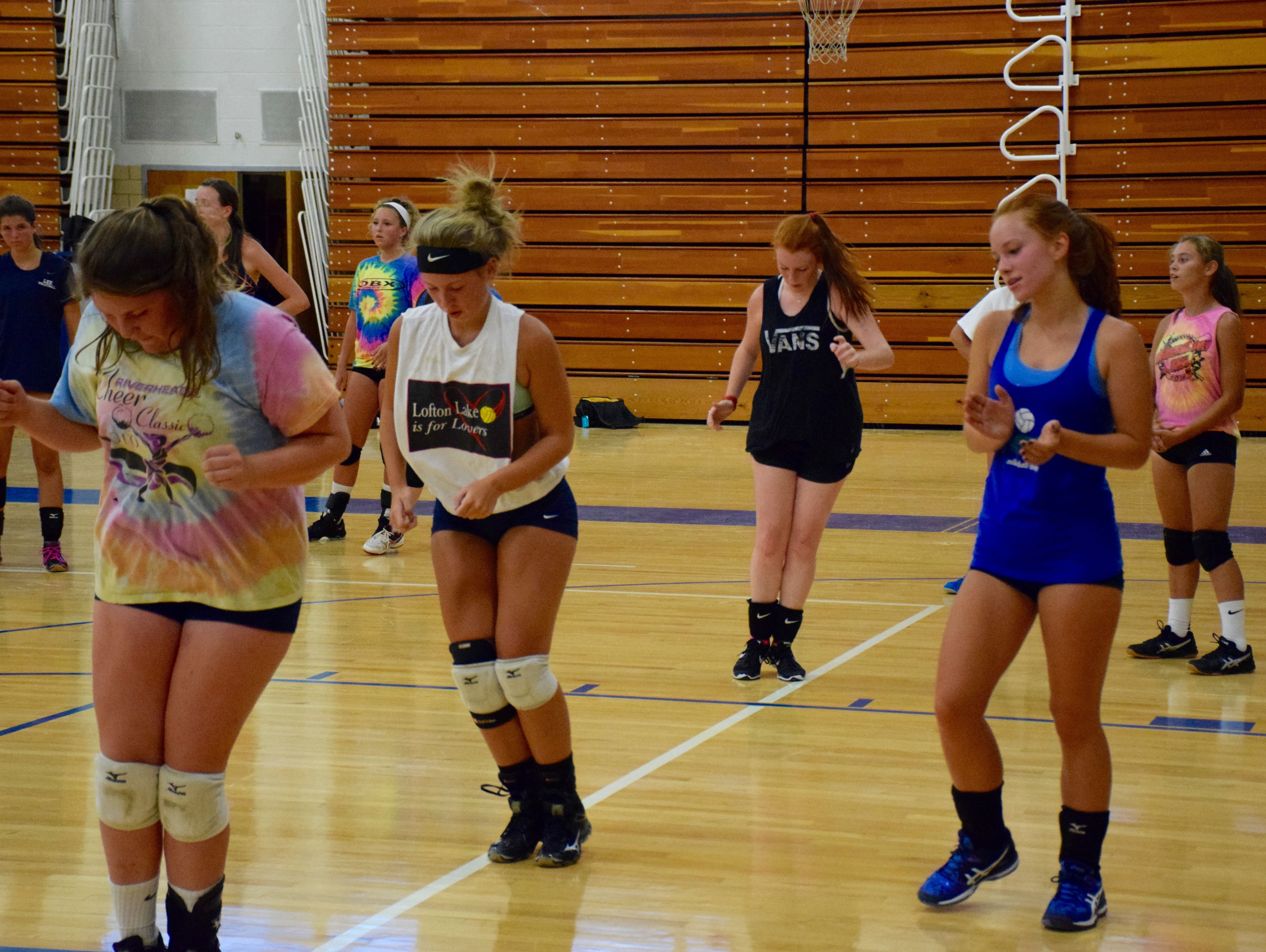 Robert E. Lee volleyball player Grace Warren, right, encourages other players during an agility drill at the first day of practice and tryouts for the Lee Ladies on Monday, Aug. 1, 2016, in Staunton.
