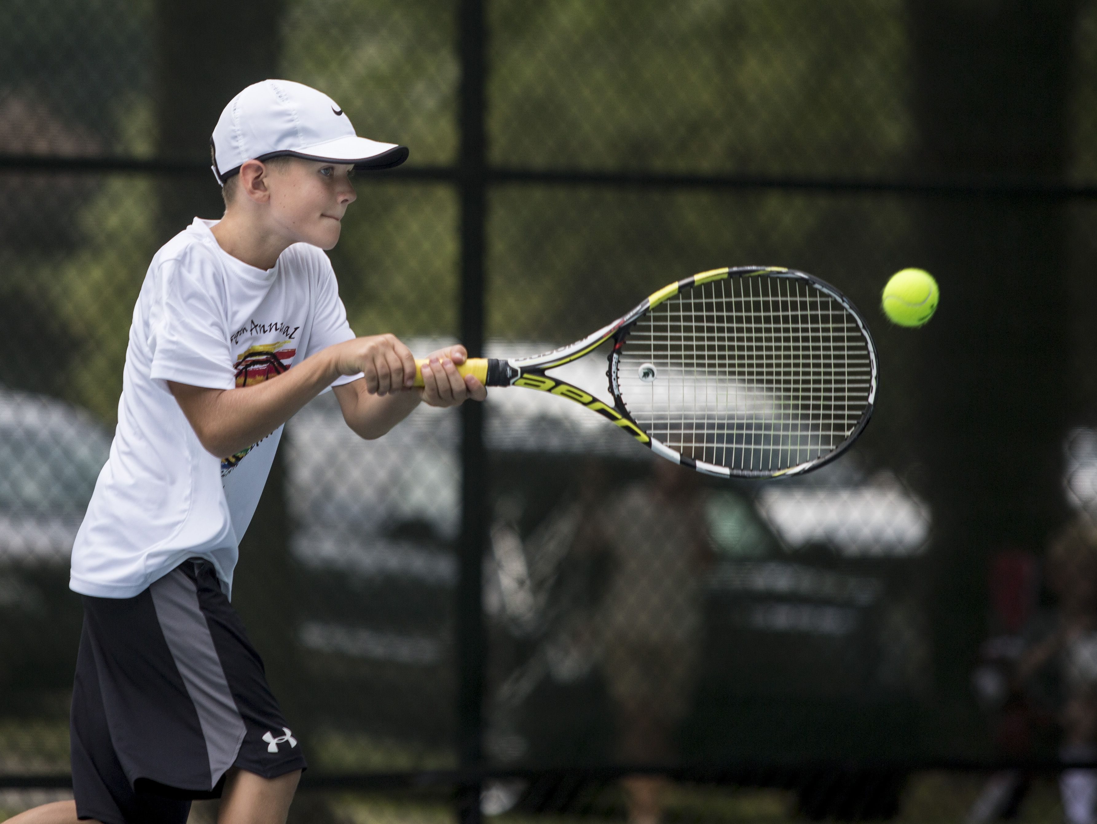 Dylan Distelrath, 10, of St. Clair, returns the ball during the Francis J. Robinson Memorial International Tennis Tournament Friday, August 5, 2016 at Sanborn Park in Port Huron.