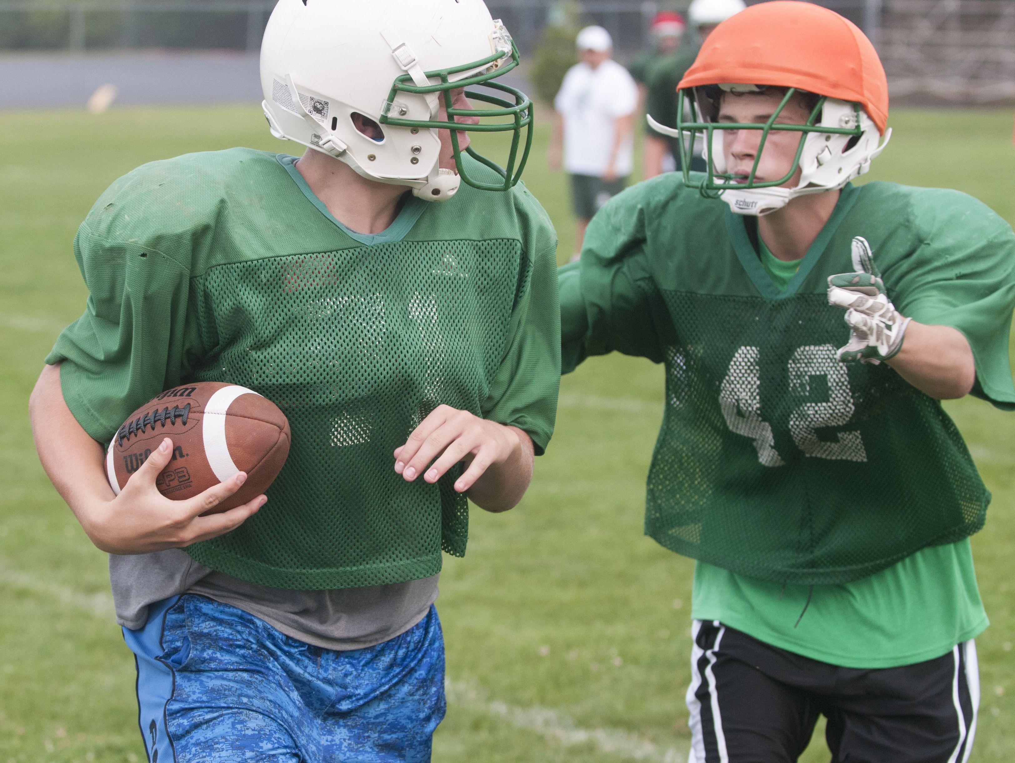 Brown City's David Halbert runs the ball as Sebastian Blevins follows Thursday, Aug. 11, 2016 during their football practice at Brown City High School.