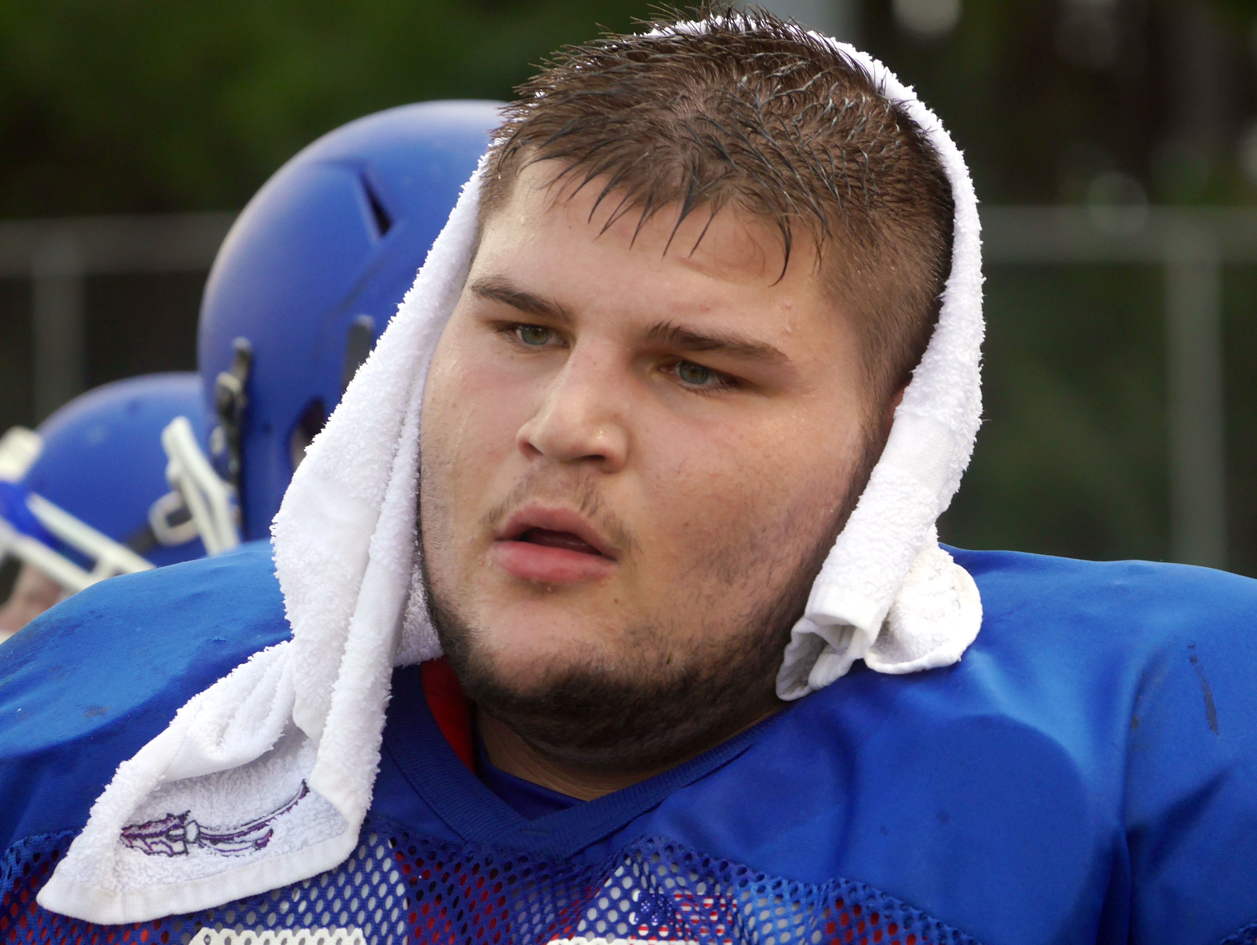 Fort Defiance #66 Zachery Boyers stays cool with a cold towel over his head during their scrimmage against James River at the Riverheads High School 2016 football jamboree on Aug. 20, 2016.
