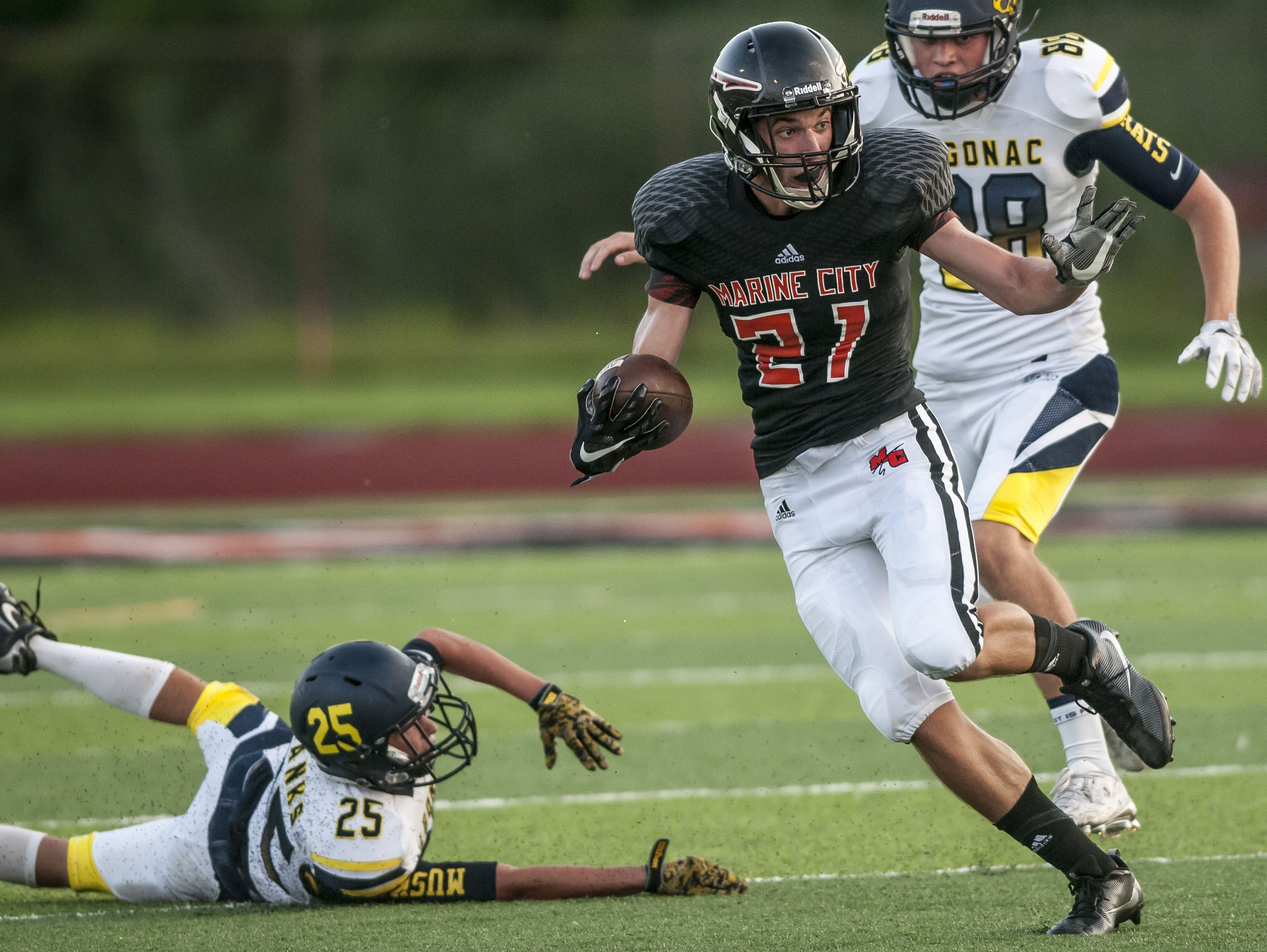 Marine City's William Pastalis breaks past several Algonac defenders as he drives the ball down field during a football game Thursday, August 25, 2016 at East China Stadium.