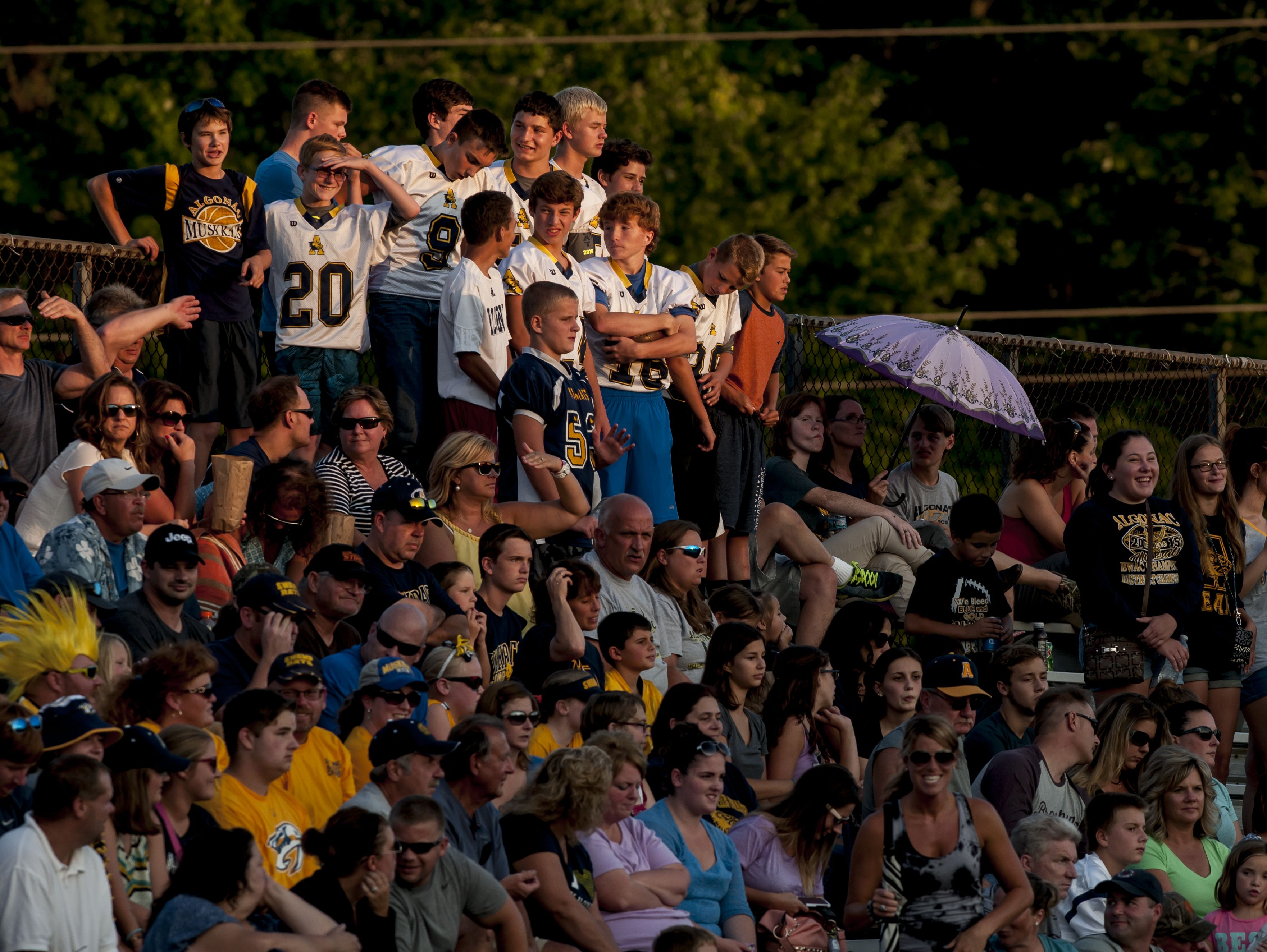 Fans watch from the stands as the sun sets during a football game Thursday, August 25, 2016 at East China Stadium.