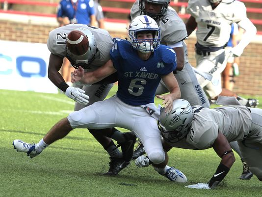Louis Raines of St. Xavier can only watch the ball as it pops out of his grasp. St. John Bosco recovered the fumble and went on to score on the drive. St. Xavier took on St. John Bosco out of California as part of the Skyline Crosstown Showdown at Nippert Stadium (Photo: Brandon C. Severn, The Enquirer)