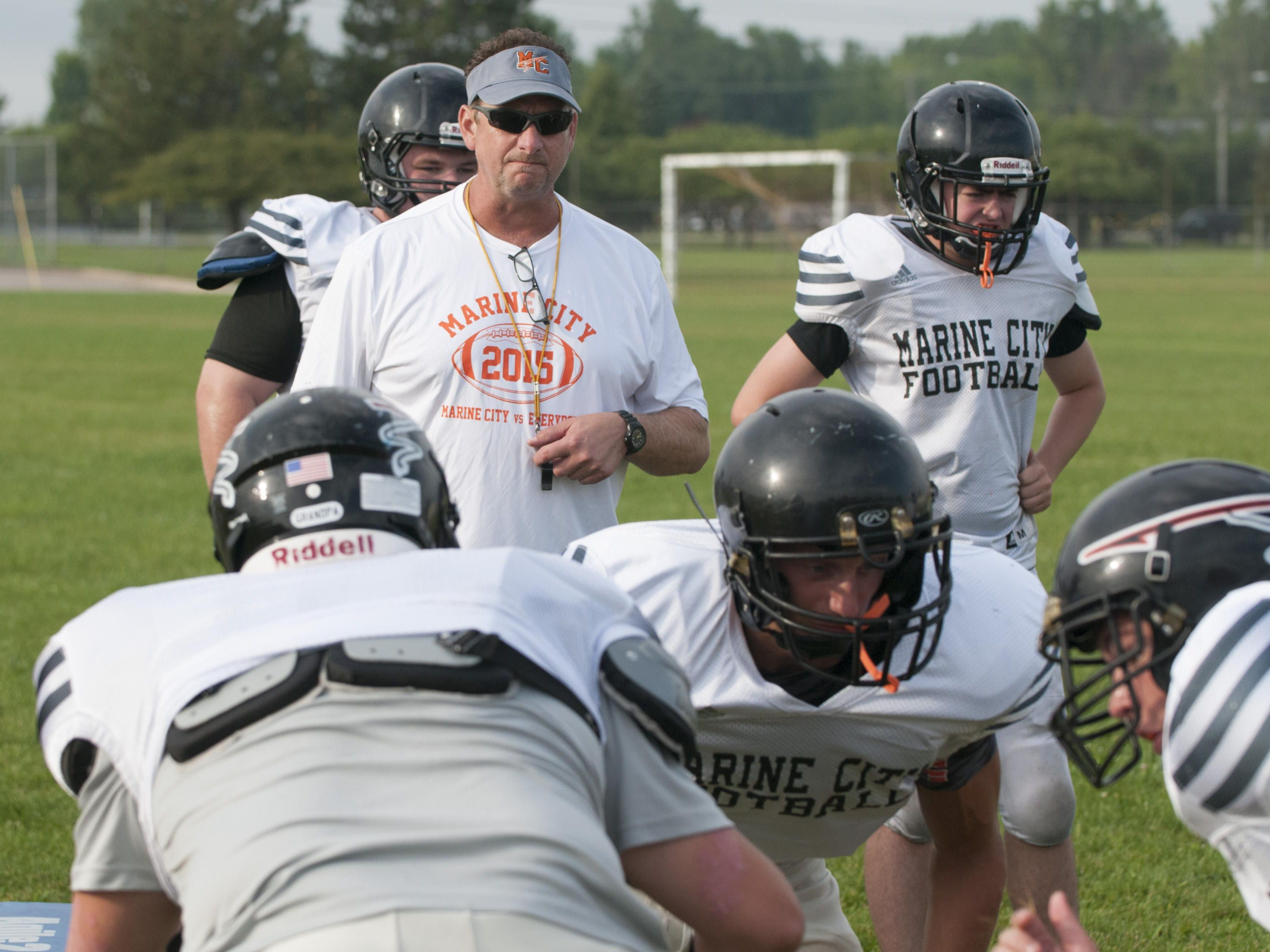 Marine City coach Ron Glodich watches his players run through a blocking drill Monday, Aug. 15, 2016 at Marine City High School.