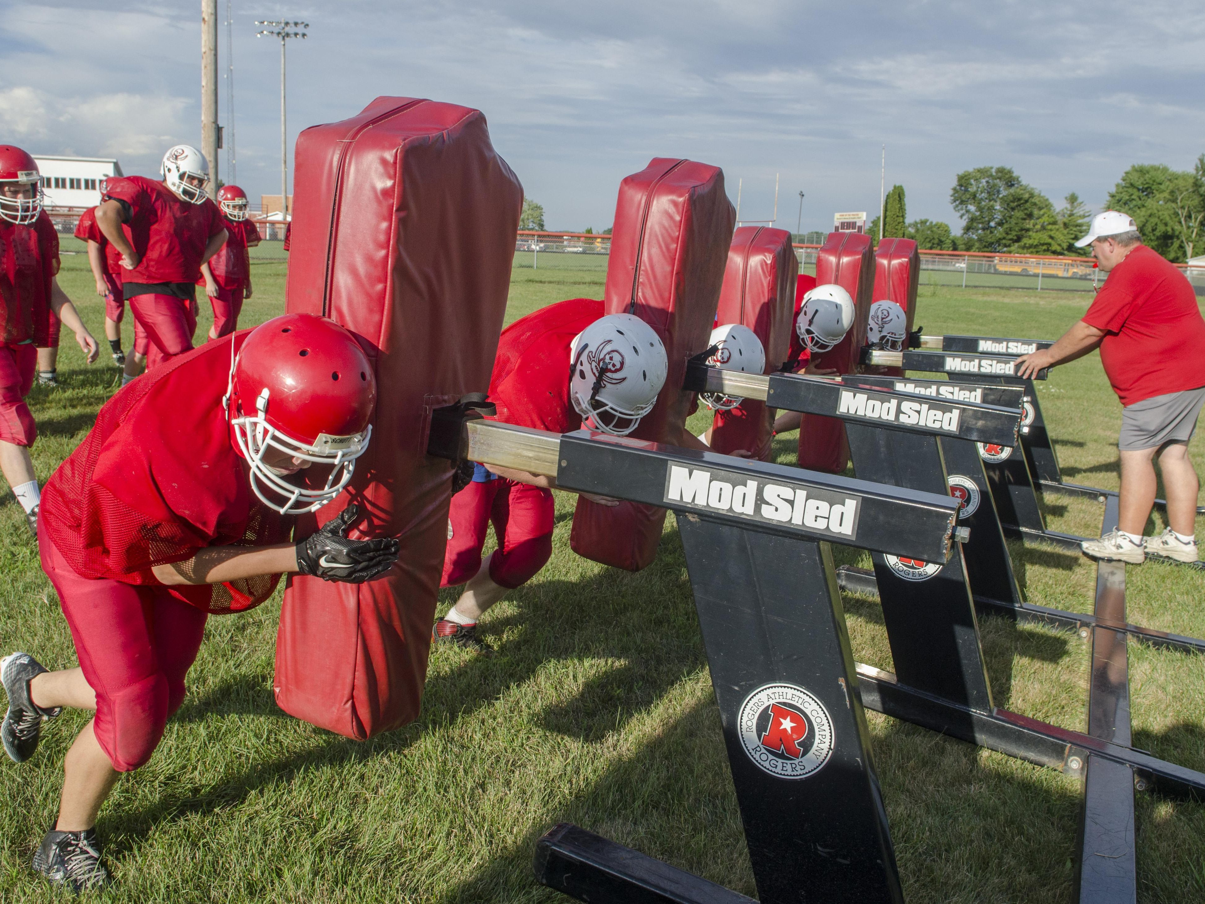 Peck's head coach Rob McDaniel runs his players on a sled Wednesday, Aug. 17 during their football practice at Peck High School.