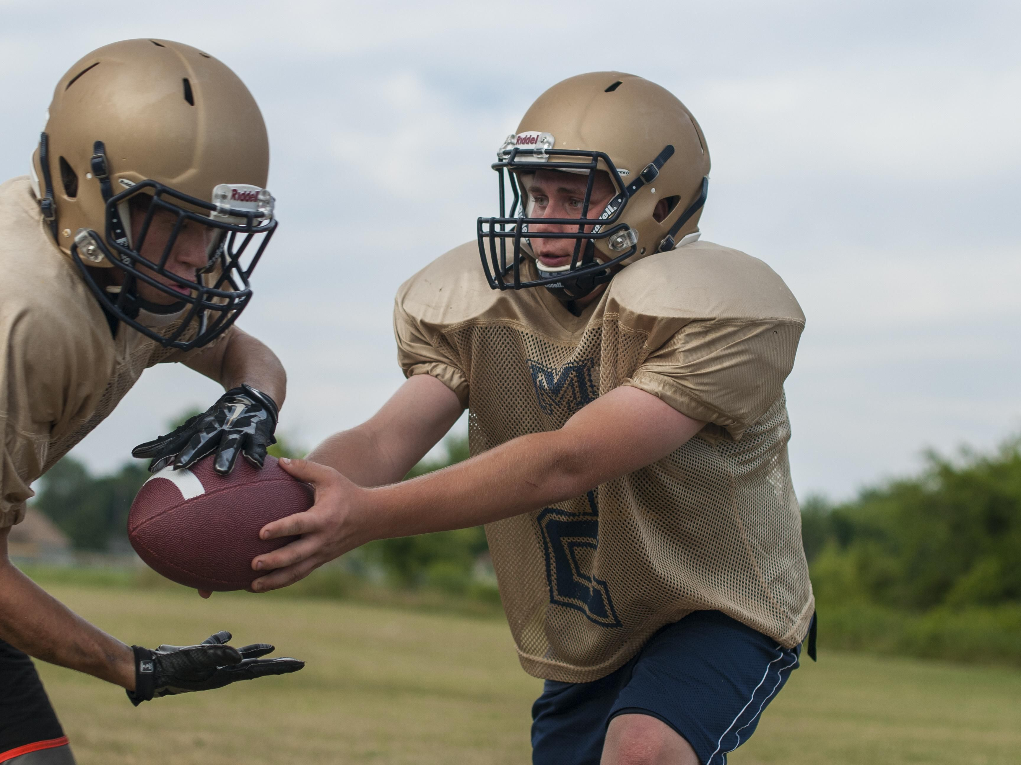 Brandley Strunk hands the ball off to John Grigg Thursday, Aug 11, during practice at Memphis High School.