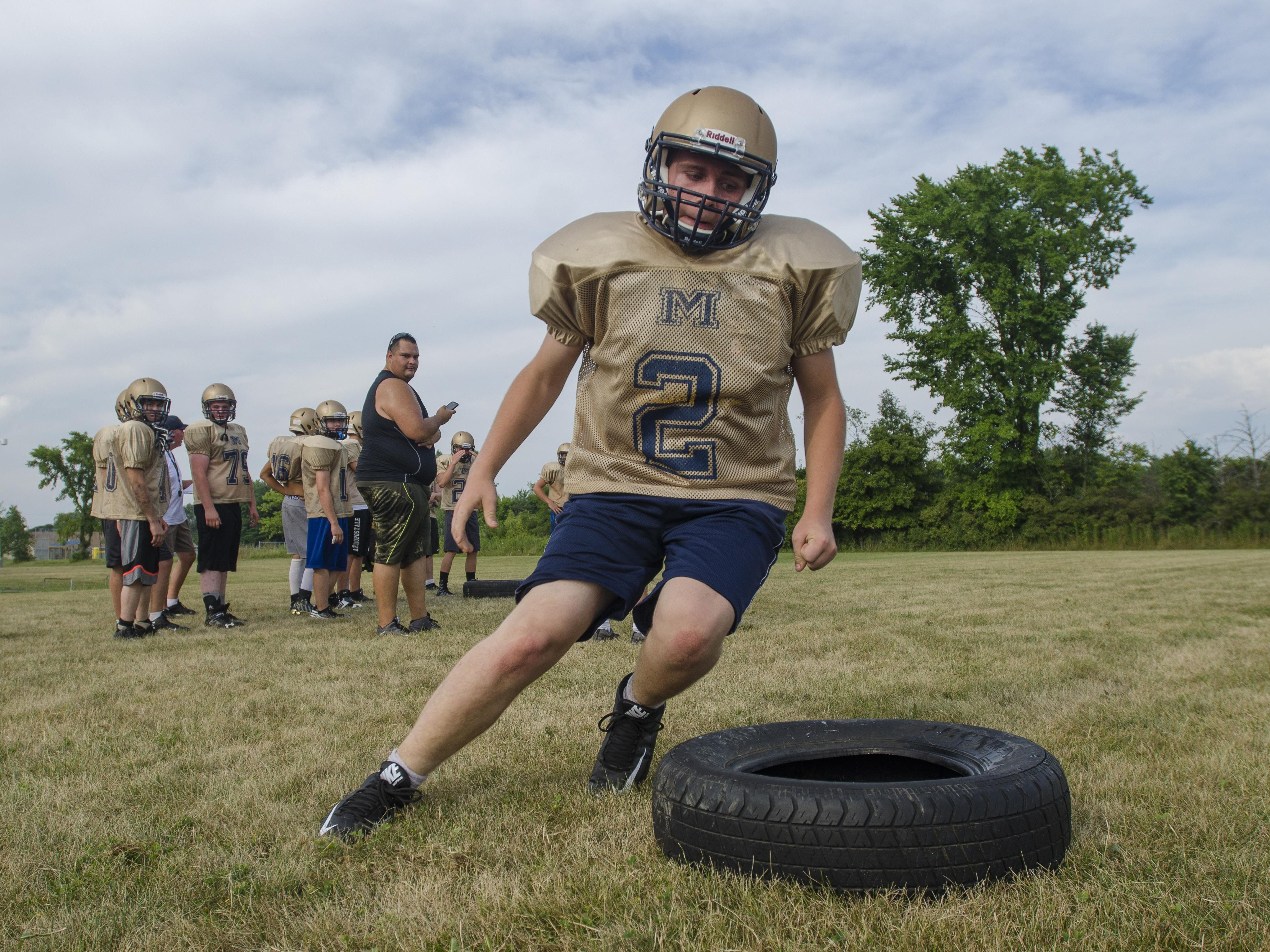 Bradley Strunk runs around a tire Thursday, Aug 11, during practice at Memphis High School.
