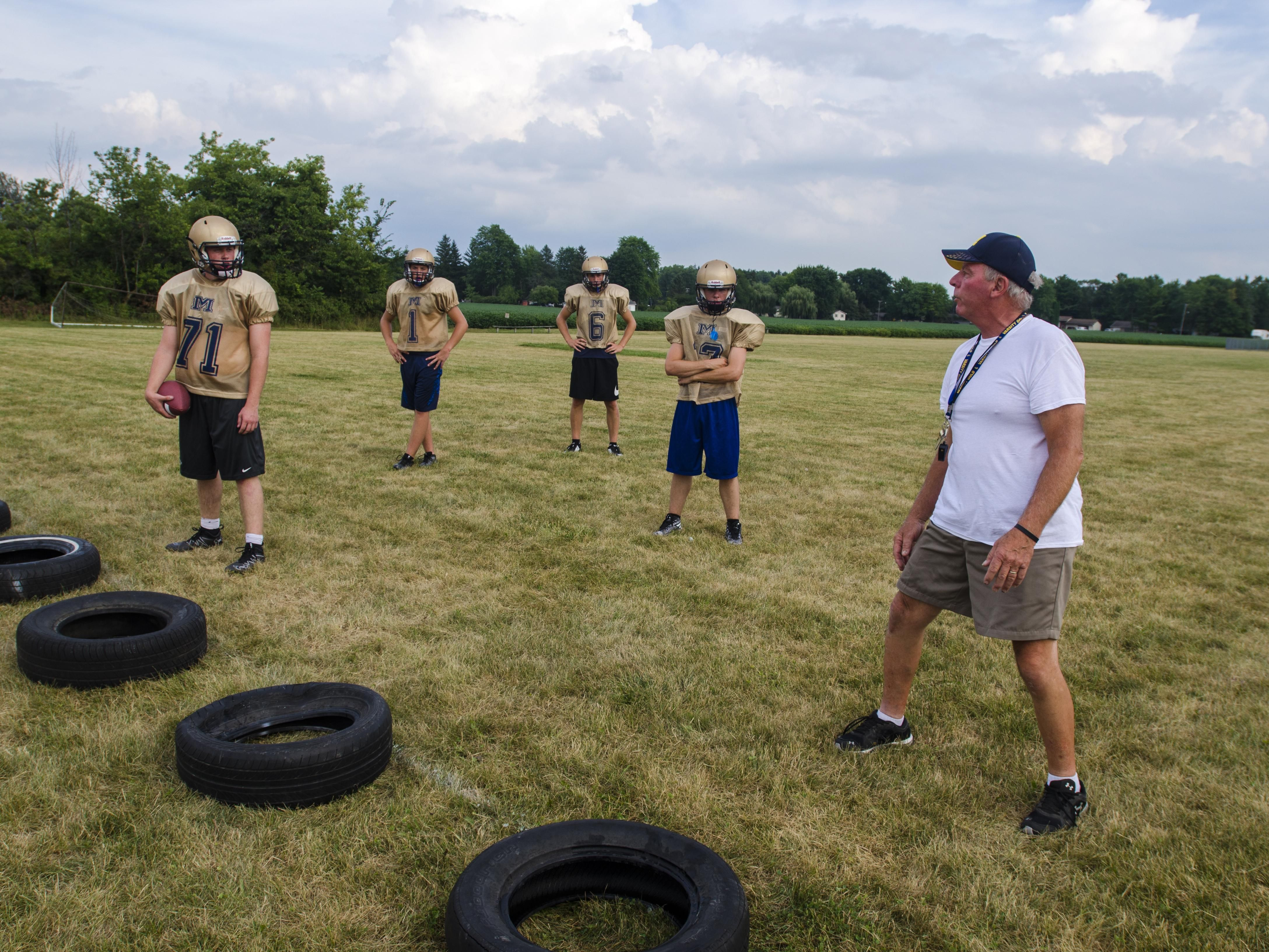 Head coach Larry Larry Badke talks to his players Thursday, Aug 11, during practice at Memphis High School.