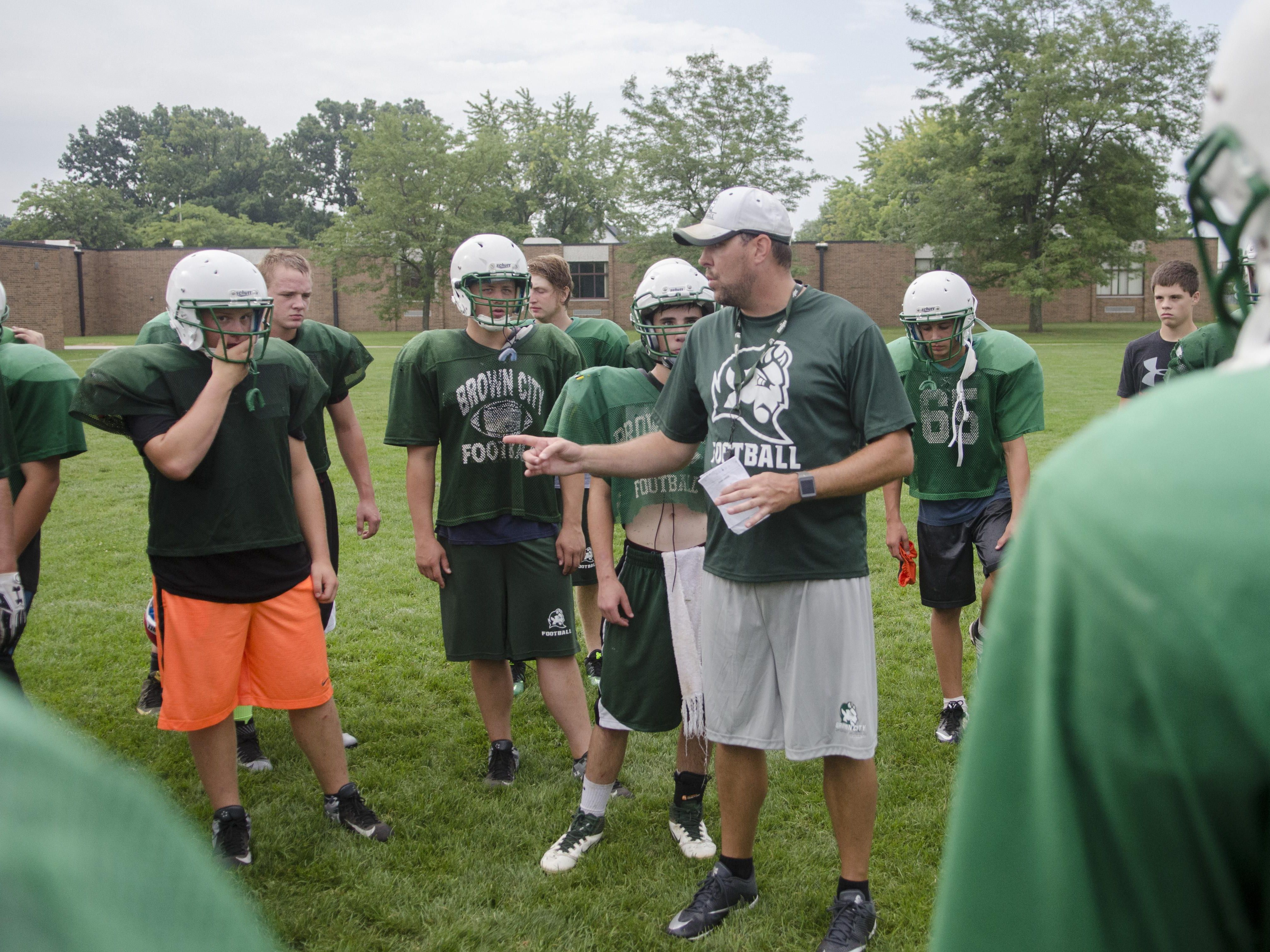 Brown City coach Aren Cooper talks to his players Thursday, Aug. 11, 2016 during their football practice at Brown City High School.