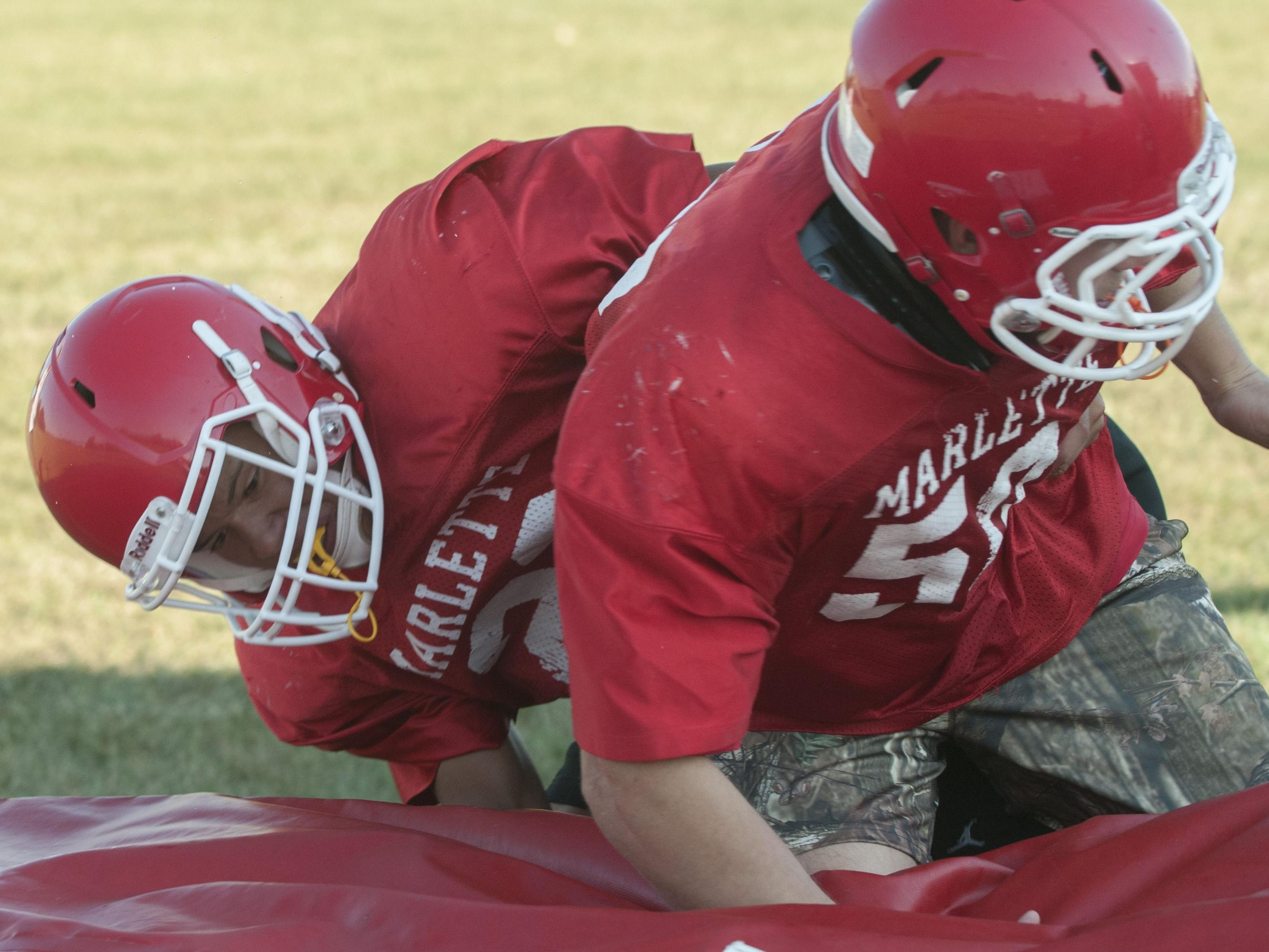 Marlette's Isaac Dale tackles teammate Chorben Chisholm Wednesday, Aug. 10 , 2016 during their football practice at Marlette High School.