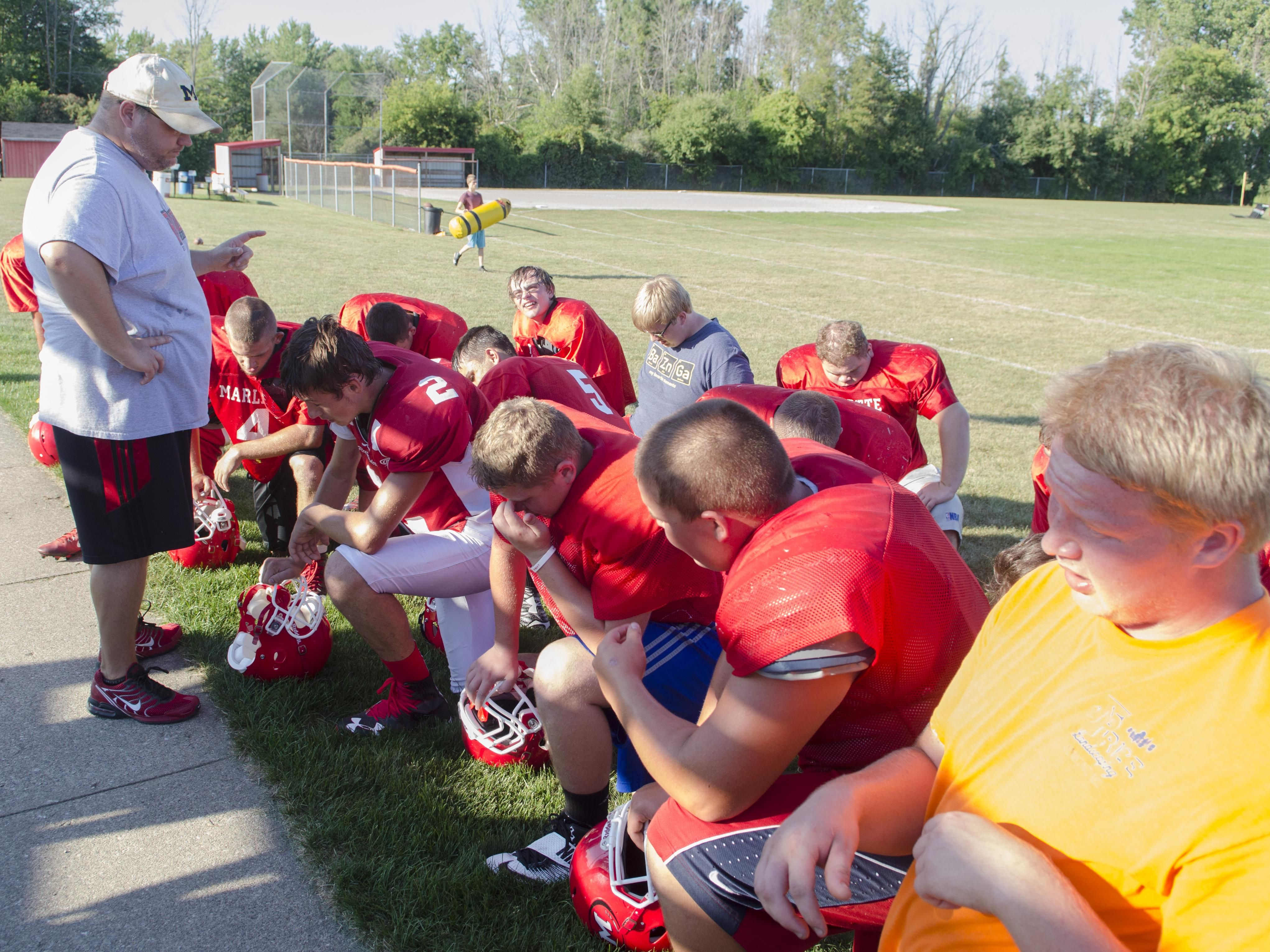 Marlette coach Dennis Lester talks to his players Wednesday, Aug. 10 , 2016 after their football practice at Marlette High School.