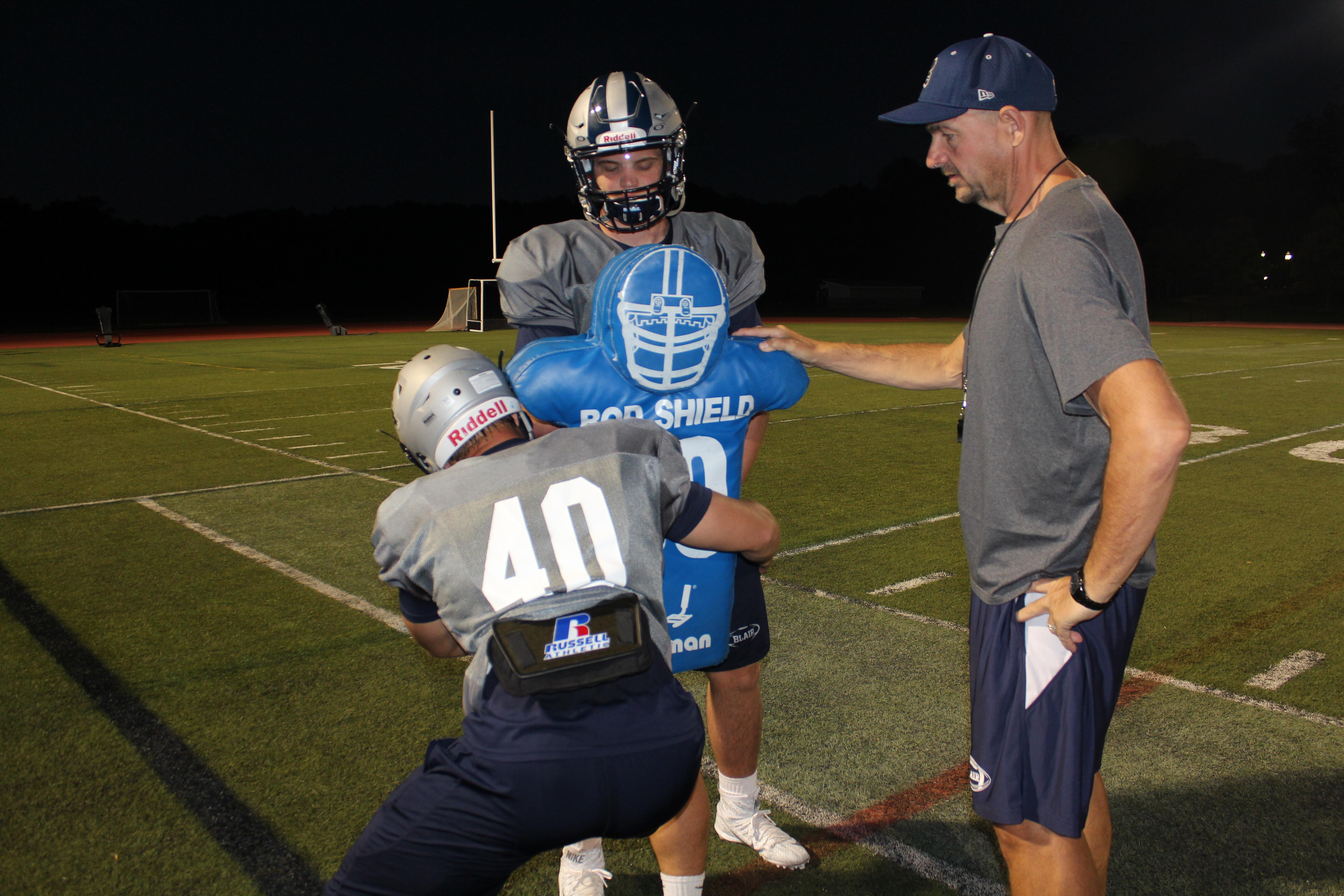 Blair Academy coach Jim Saylor works with Coach Jim Saylor with senior captains Nick Mosco and Chase Singletary and a tackling dummy (Photo: Blair Academy)