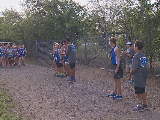 After Southwest Christian School cross country runners cross the finish line, they take a moment to recover, and then go encourage every other runner who hasn't yet finished. (Photo: WFAA)
