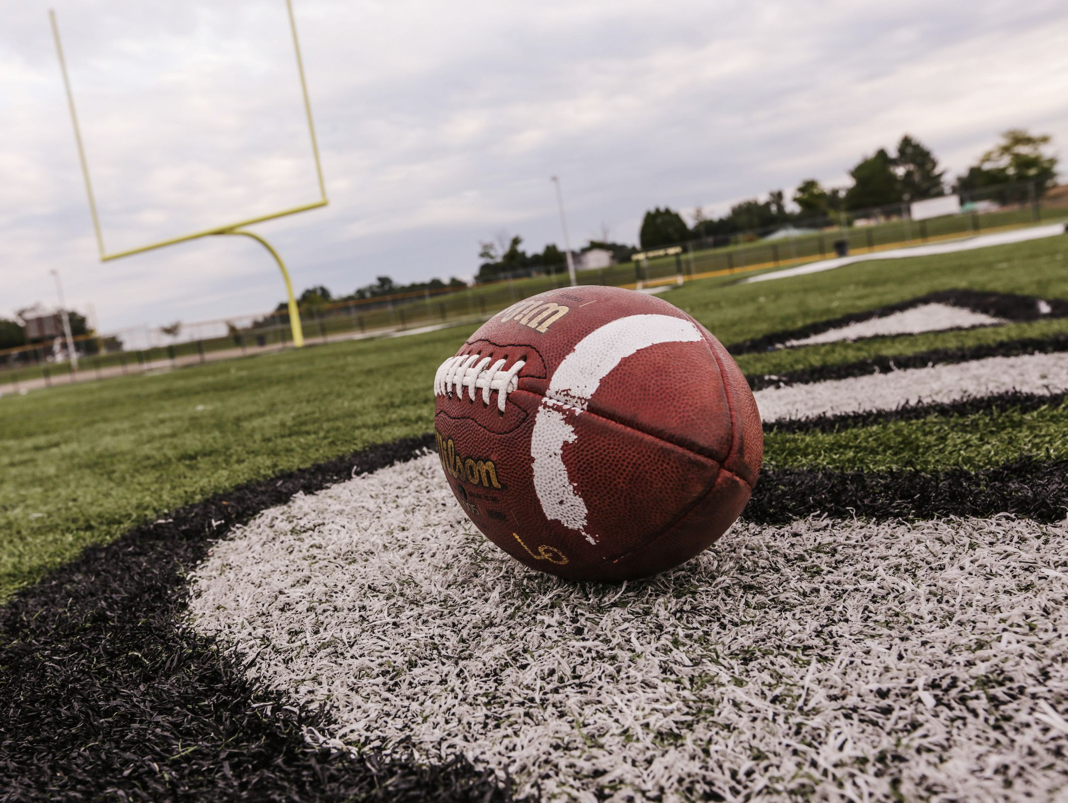 A football lays on the field in view of the end zone at a high school.