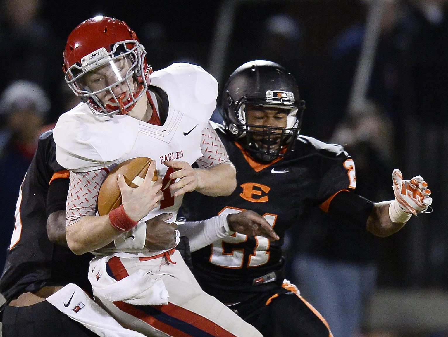 Brentwood Academy quarterback Jeremiah Oatsvall (4) tries to get past Ensworth defensive back P.J. Settles. left, and cornerback Donovan Sheffield (21) during the fourth quarter at Ensworth High School on Friday, October 31, 2014, in Nashville, Tenn.