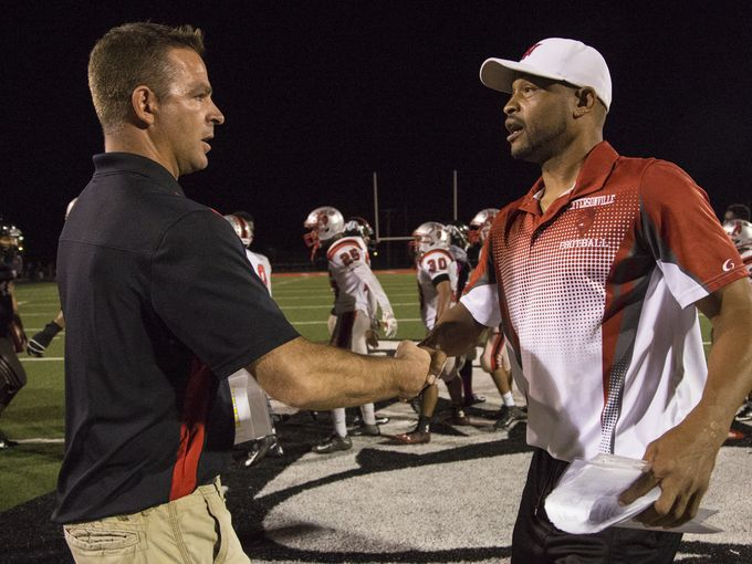 New Albany coach Sean Coultis, left, meets with Jeffersonville coach Alfonzo Browning at midfield following a game between the Bulldogs and Red Devils last season.