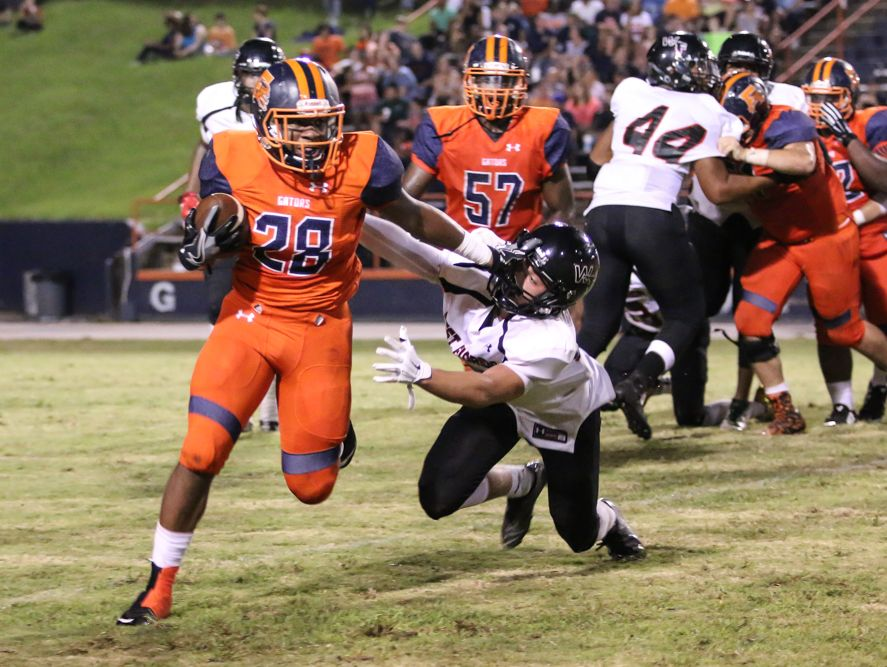 Escambia's Ray Samuel (28) stiff arms a West Florida defender to get past him Thursday night at Escambia High School's Emmitt Smith Field.