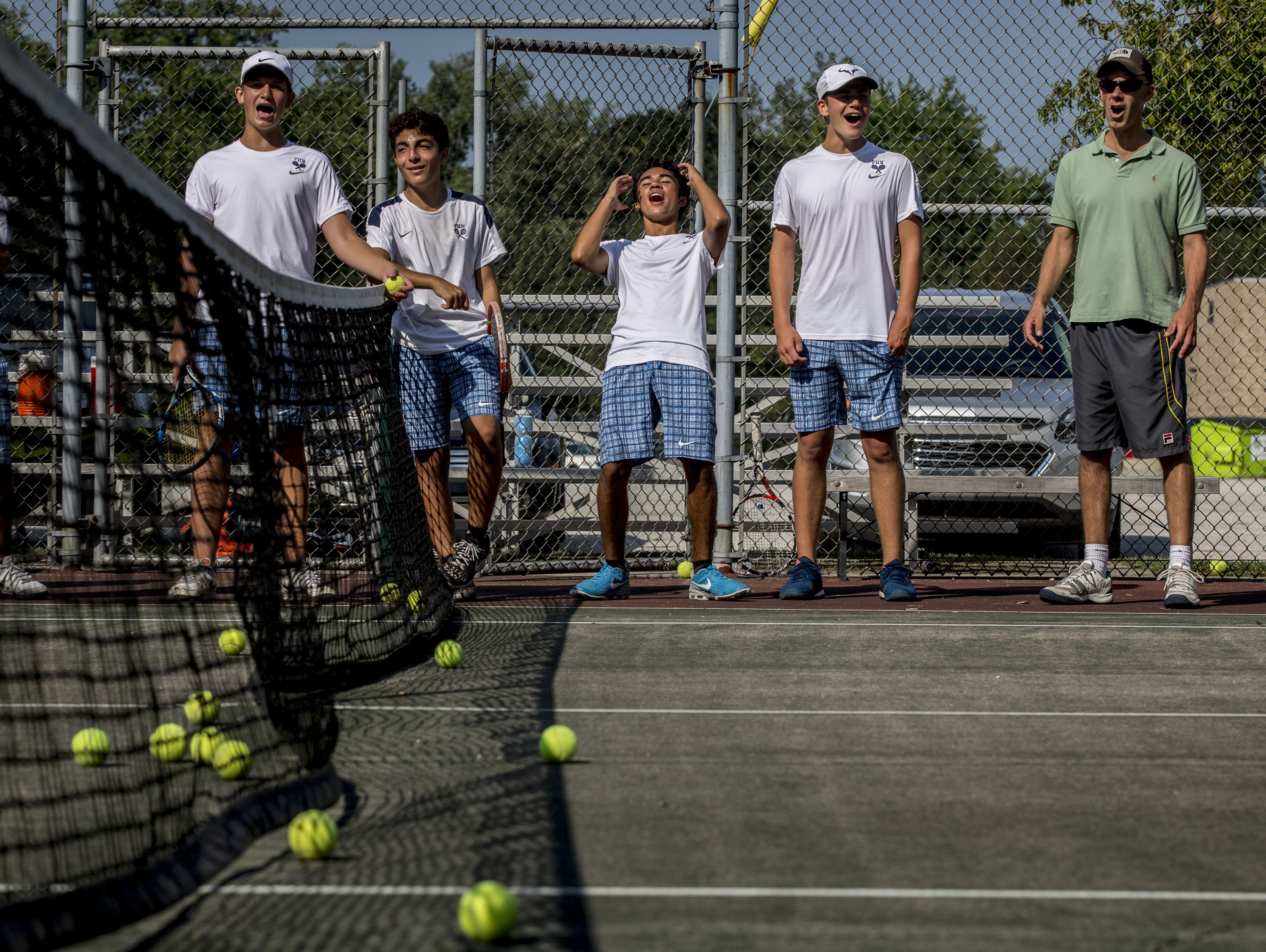 Port Huron Northern coach Chris Smith, right, reacts along with players as they watch a match during tennis practice Tuesday, August 30, 2016 at Port Huron Northern High School.