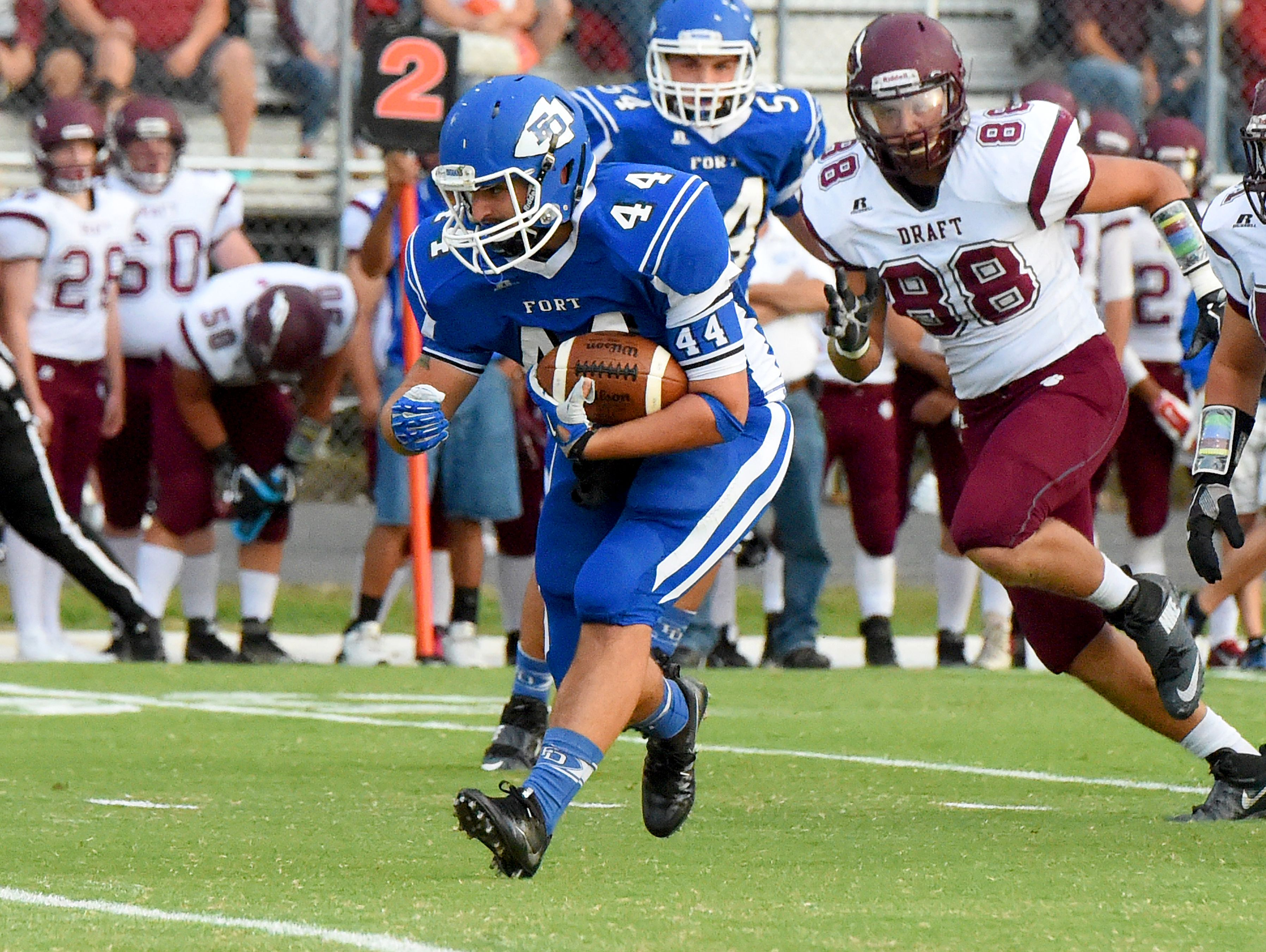 Fort Defiance's Austin Fitzwater runs the ball as Stuarts Draft's John Gumann pursues during a football game played in Fort Defiance on Friday, Sept. 2, 2016.