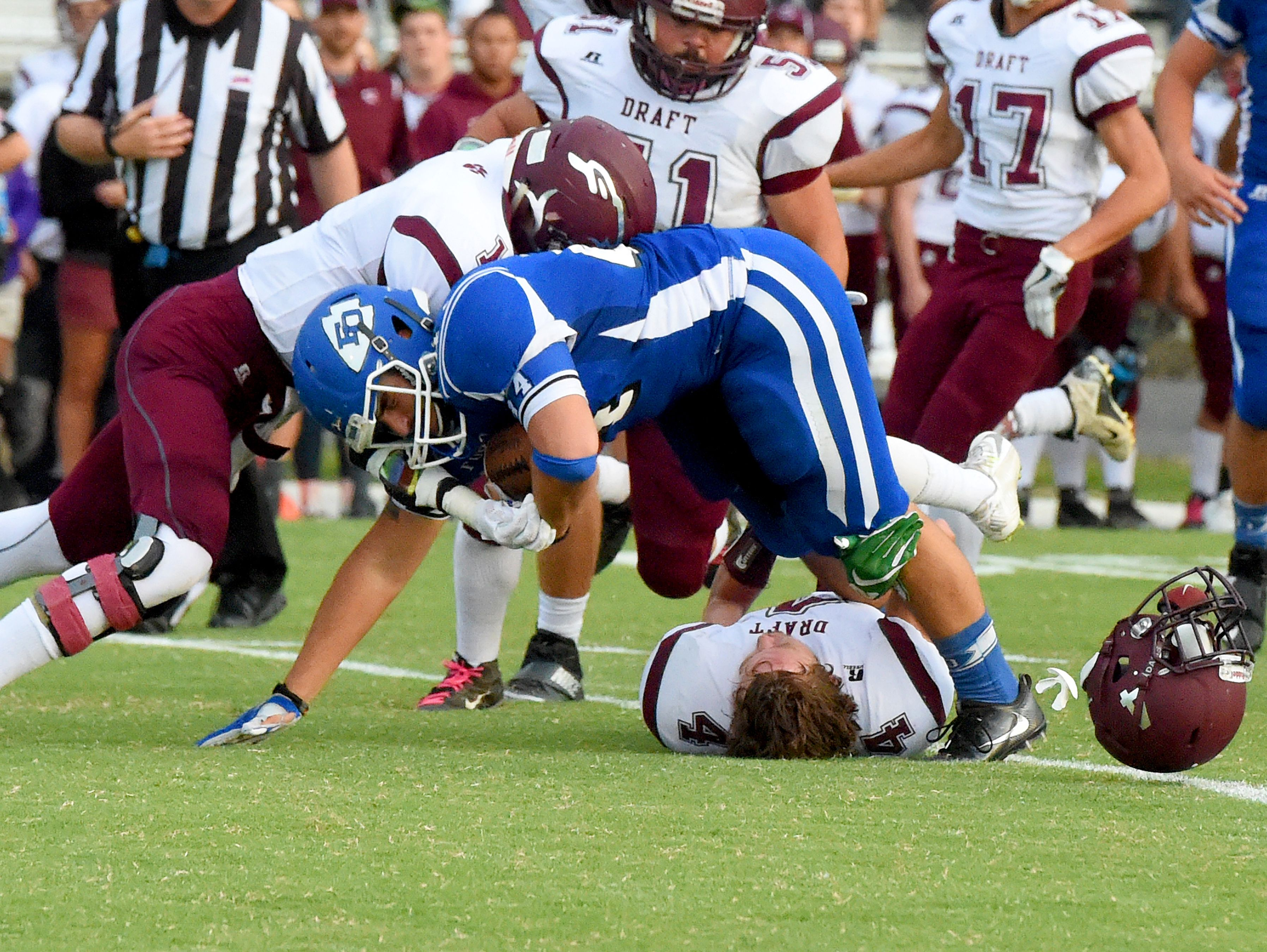 Fort Defiance's Austin Fitzwater is tackled with the football as the helmet comes off Stuarts Draft's Dalton McGann during a football game played in Fort Defiance on Friday, Sept. 2, 2016.